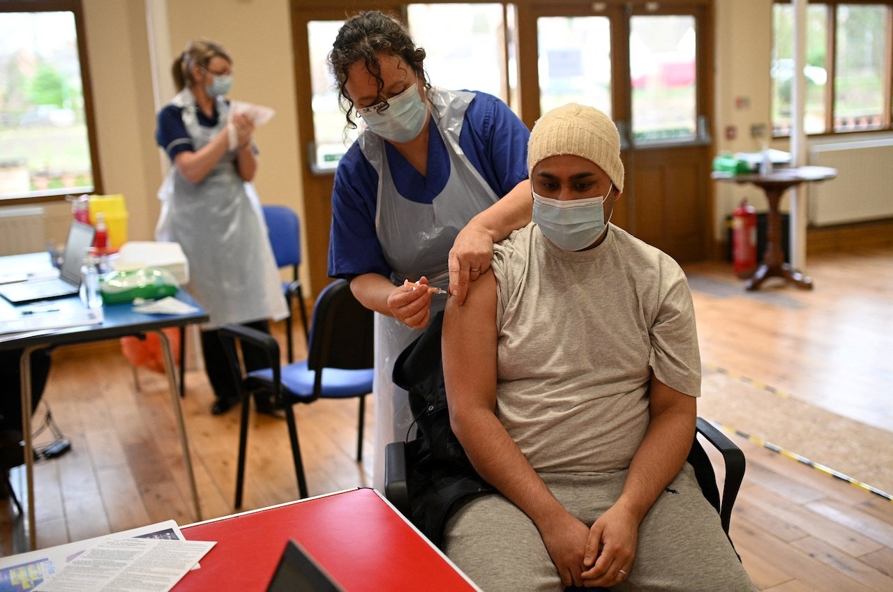 Dr Karen Worth administers a dose of the AstraZeneca/Oxford Covid-19 vaccine to a patient at a vaccination centre set up at the Fiveways Islamic Centre and Mosque in Nottingham, central England (AFP)