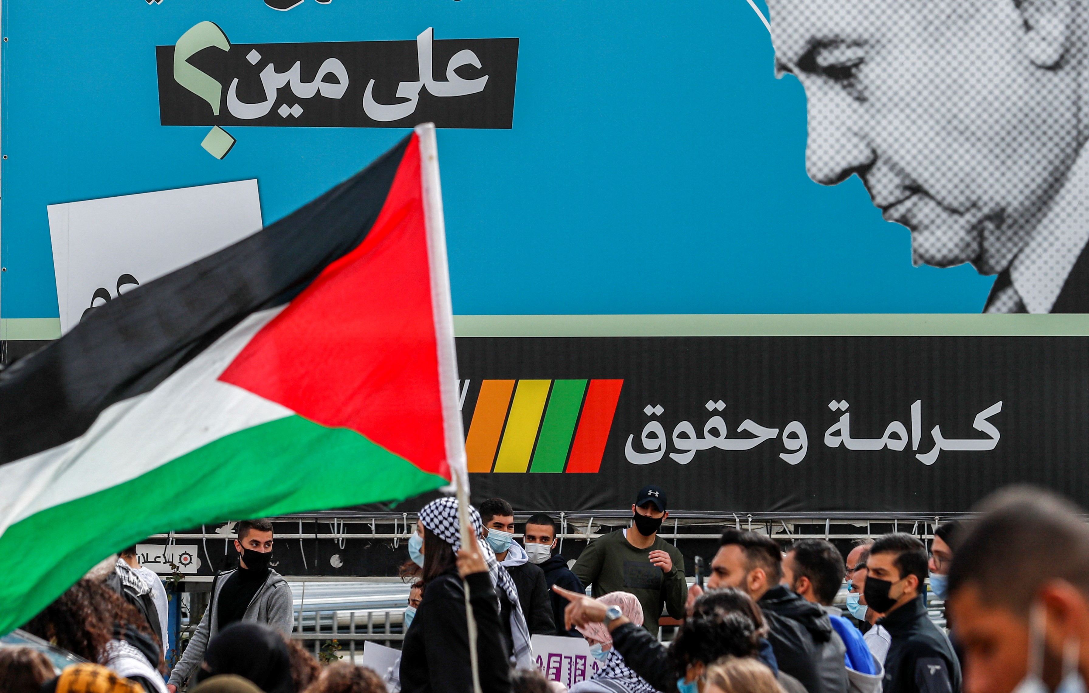 """A demonstrator holds a Palestinian flag near an electoral billboard by the predominantly Arab Israeli electoral alliance the Joint List depicting Israeli prime minister Benjamin Netanyahu with a caption reading in Arabic """"whom is he fooling?"""" during a demonstration"""