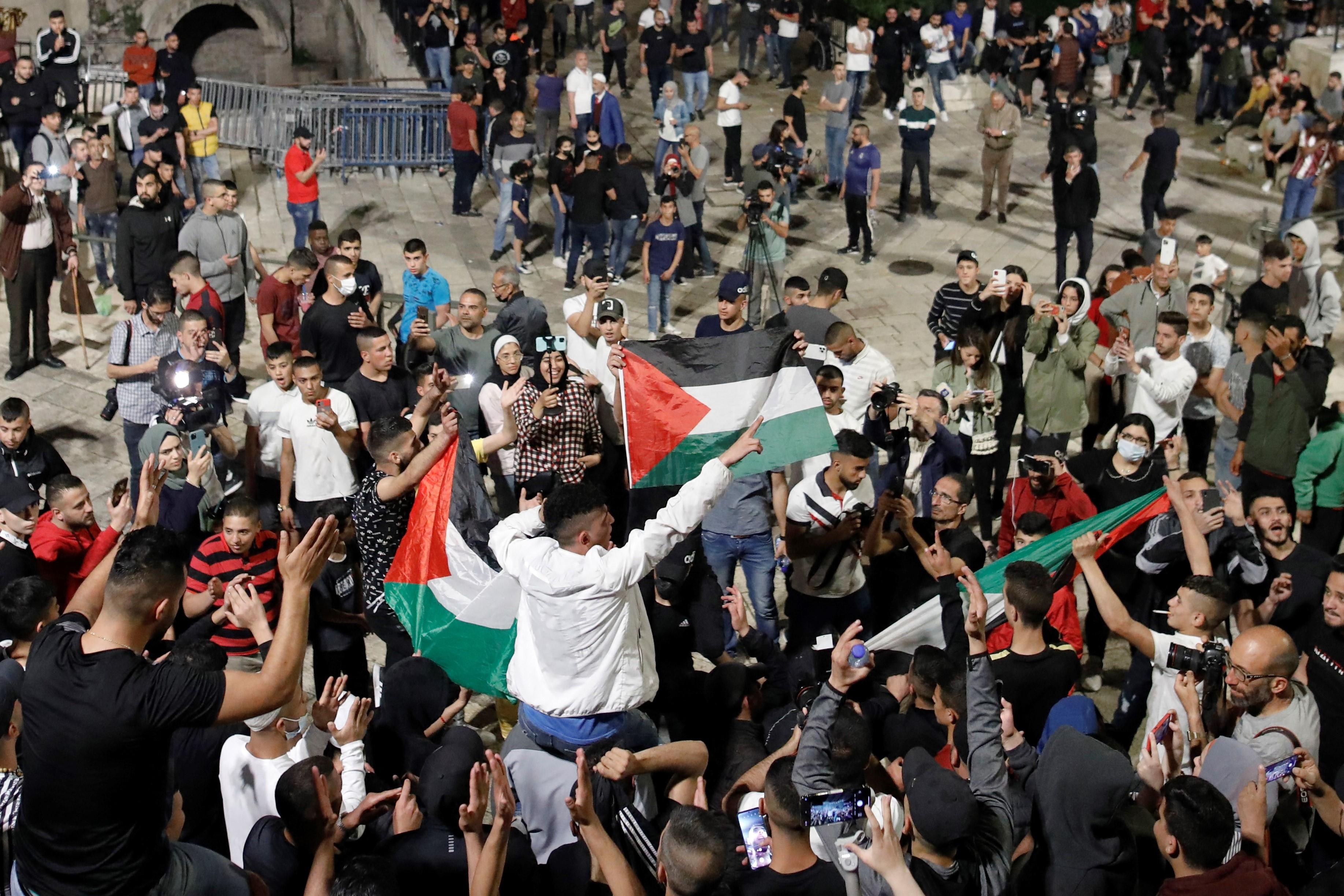 Palestinski prosvjednici podižu nacionalne zastave dok se okupljaju kraj Damaskinih vrata u starom gradu Jeruzalema, 25. aprila 2021. godine.