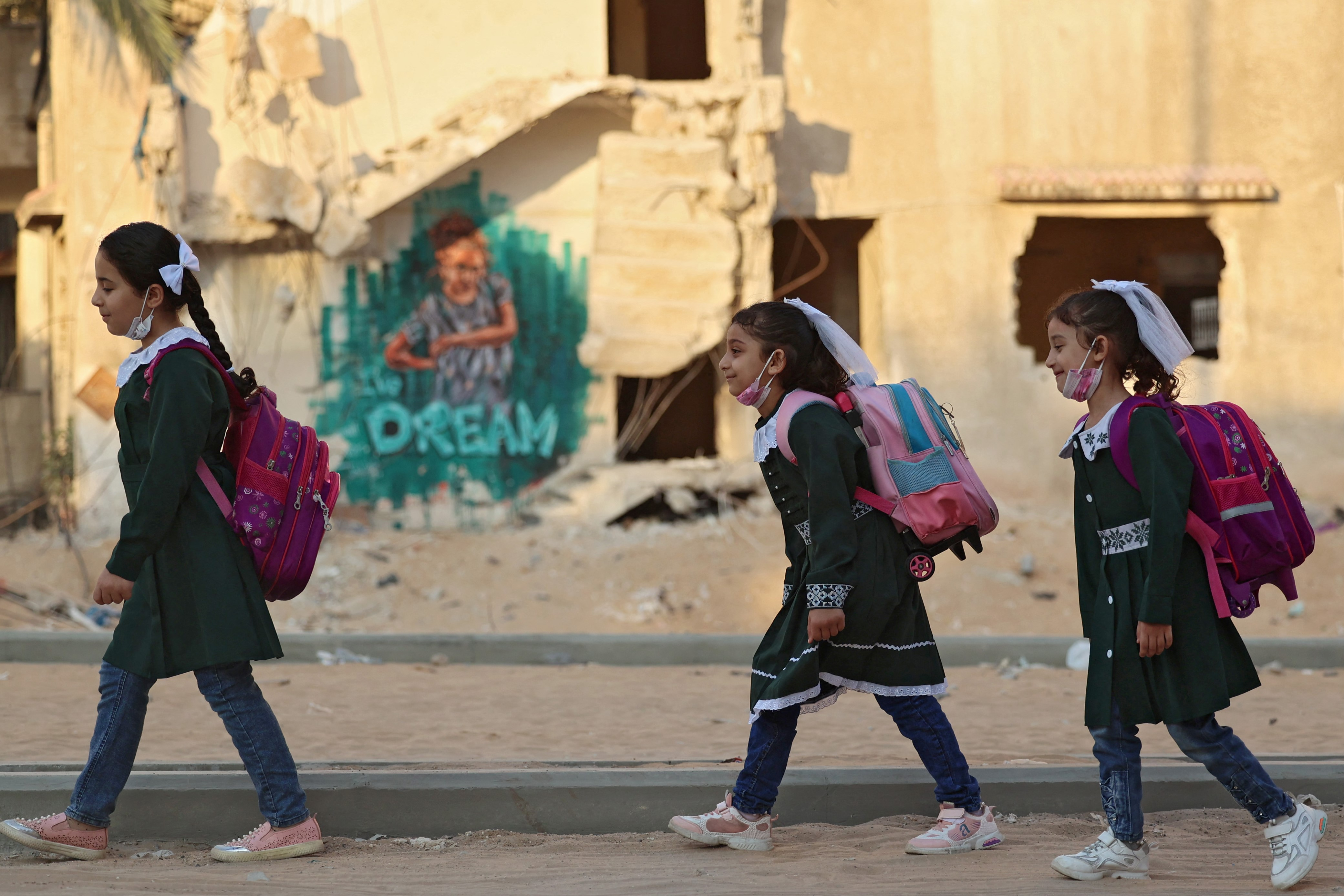 Palestinian children walk past a building, destroyed during the recent 11-day war between Israel and the Palestinian Hamas movement, on their way to school for the first day of the new scholastic year in Gaza City on August 16, 2021.