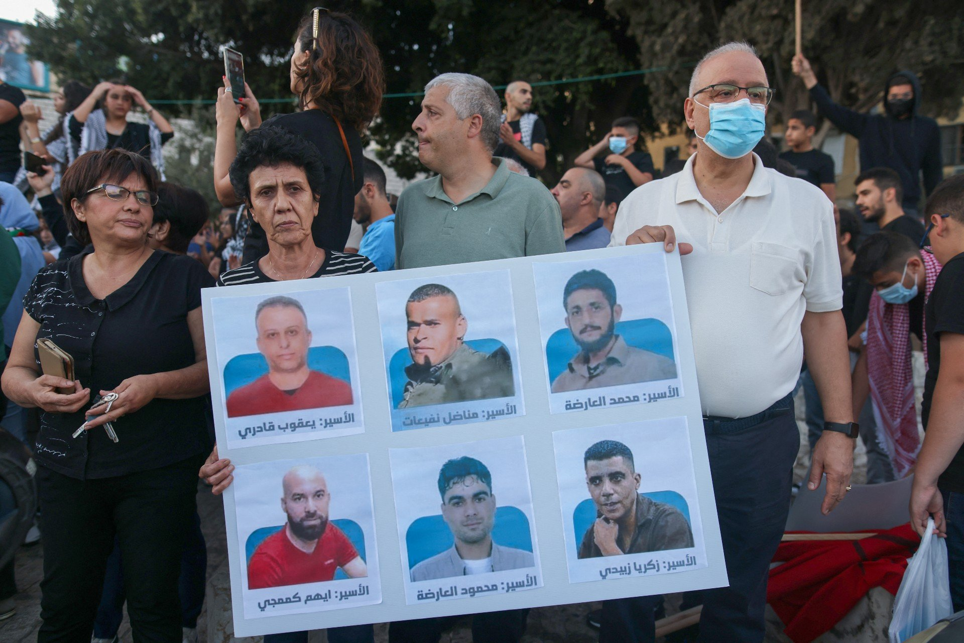 Protesters lift a placard depicting the six Palestinian prisoners, as they demonstrate to support them in the northern Israeli city of Nazareth, on 11 September (AFP)