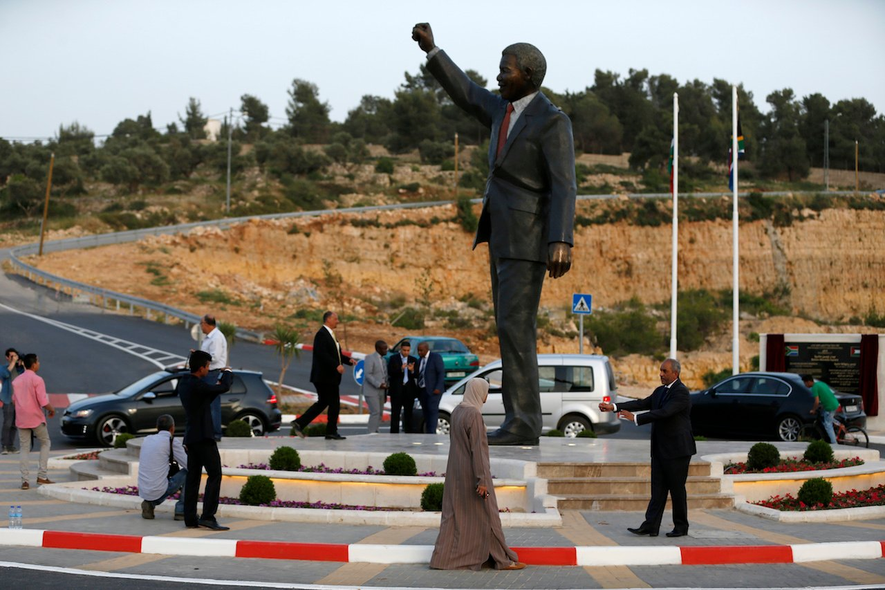 Palestinians stand next to a giant statue of Nelson Mandela following its inauguration ceremony in the West Bank city of Ramallah (AFP)