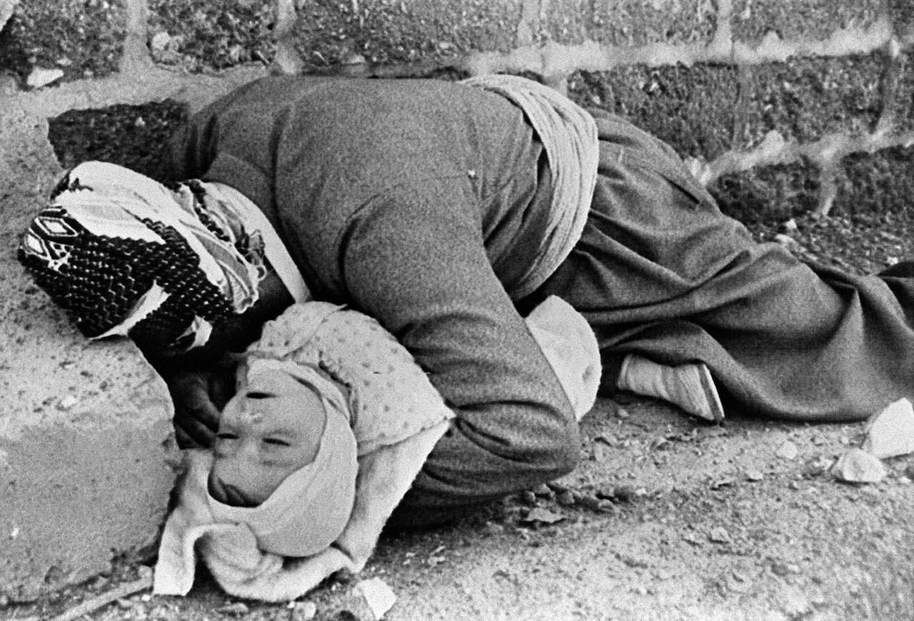 Picture dated March 20, 1988 shows a Kurdish father holding his baby in his arms in Halabja, northeastern Iraq. Both were killed in an Iraqi chemical attack on the city (AFP)