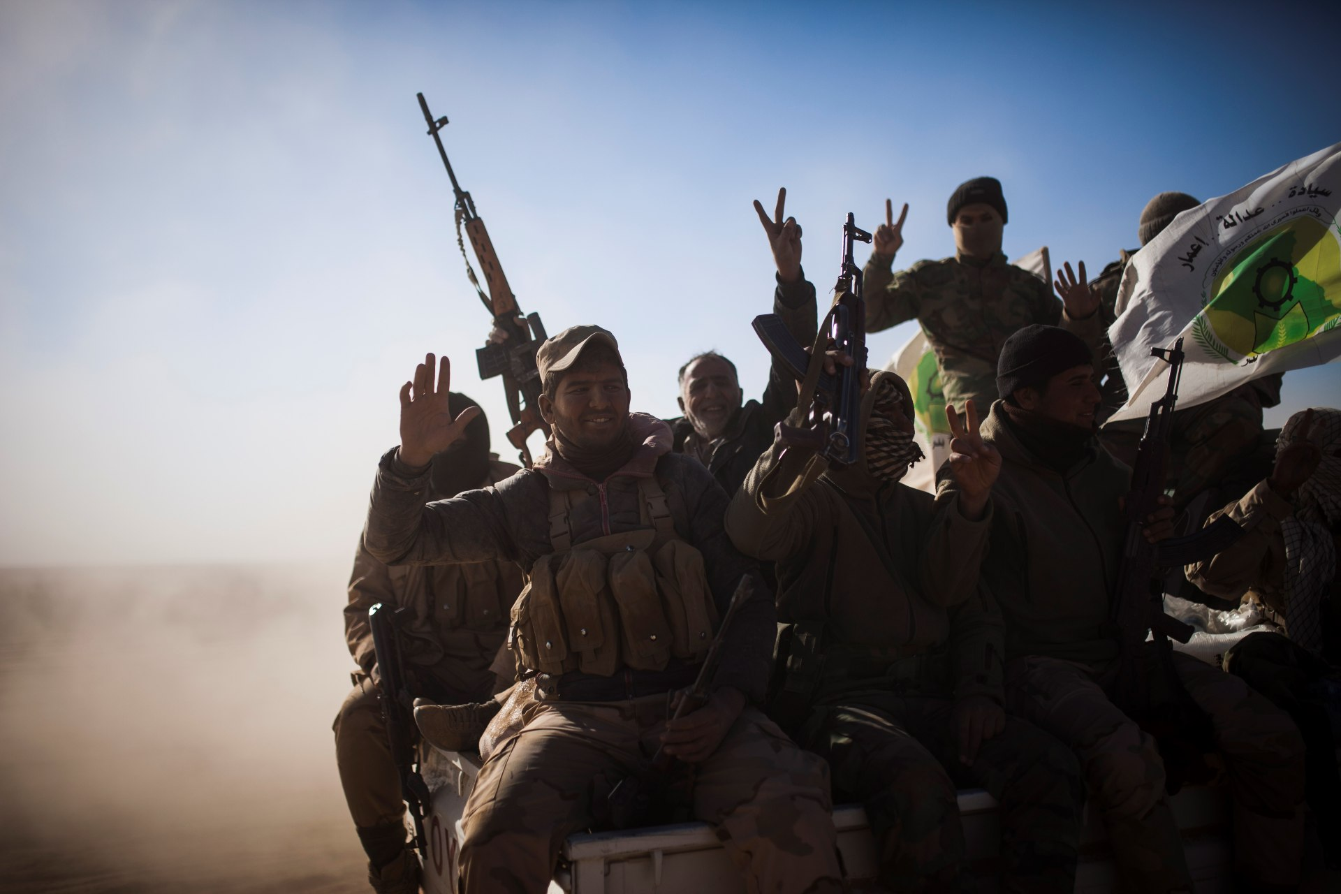 Soldiers of the Hashd al-Shaabi wave the victory sign onboard a pickup truck, on their way to Tal Afar airport in 2016 (AFP)