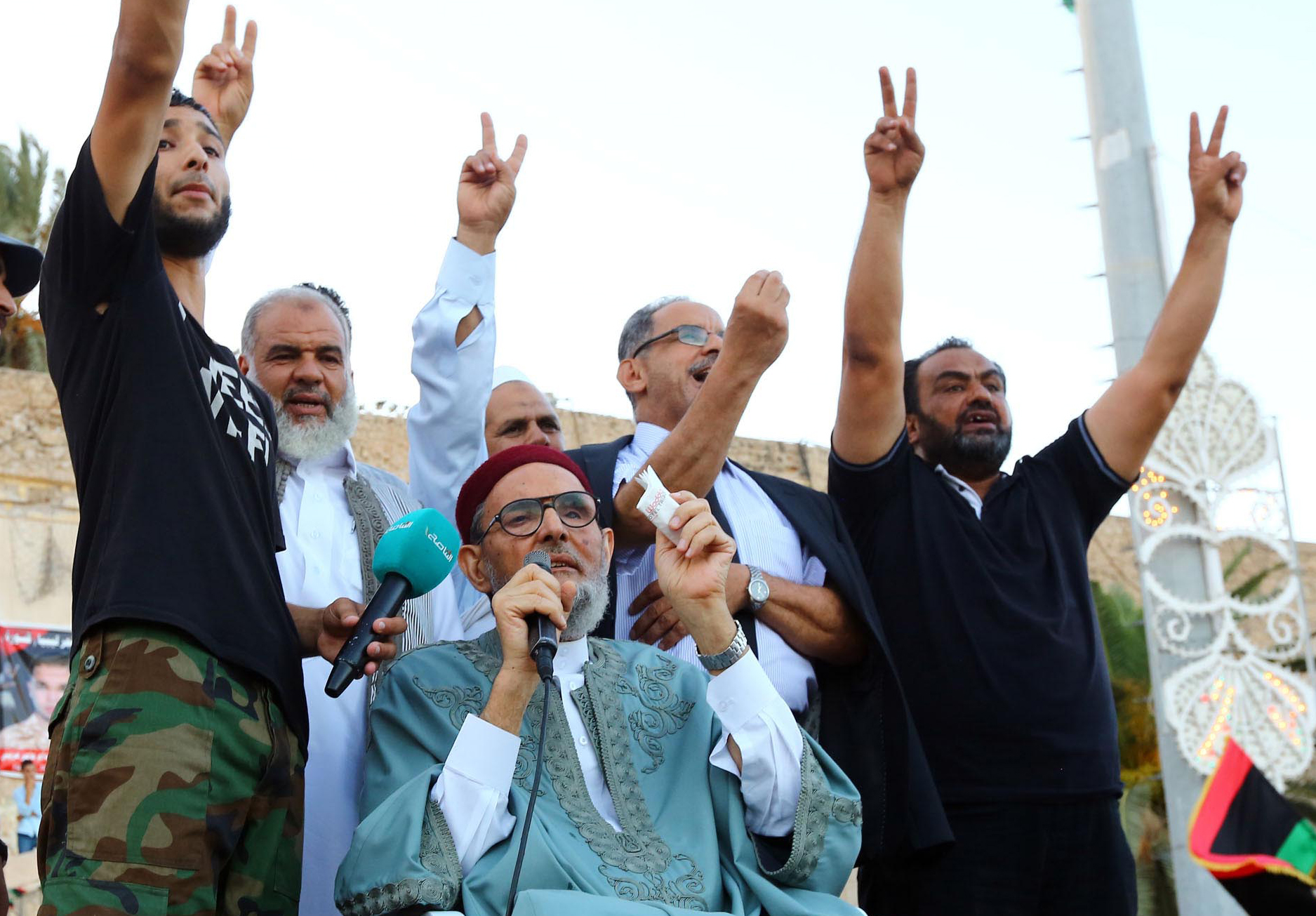 Libyan Grand Mufti Sheikh Sadiq al-Gharianni (C) speaks as others flash the sign for victory during a rally in central Tripoli's Martyr's Square in 2014 (AFP)