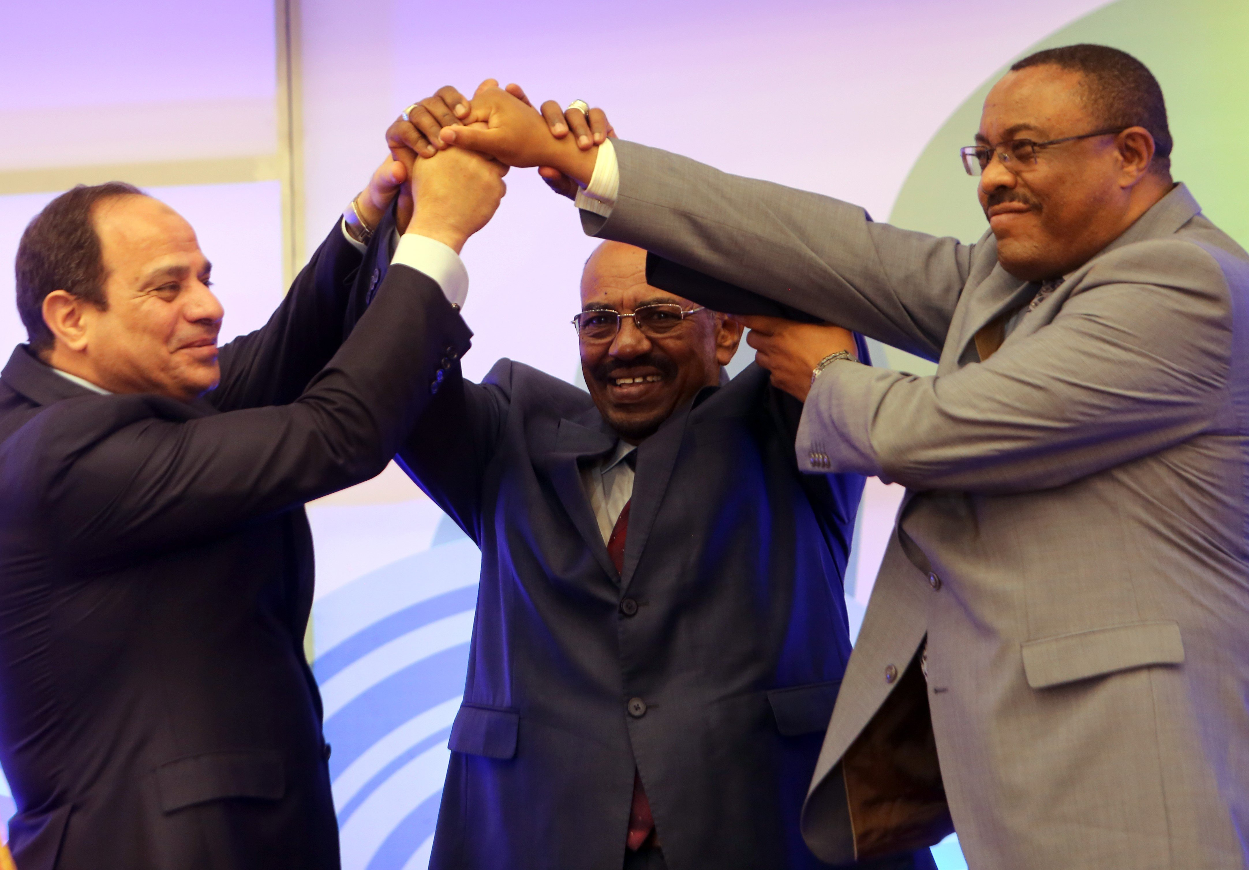 Egyptian President Abdel-Fattah al-Sisi (L), Sudanese President Omar al-Bashir (C) and Ethiopian Prime Minister Hailemariam Desalegn shake hands during a meeting in the Sudanese capital Khartoum on March 23, 2015, to sign the agreement of principles on Ethiopia's Grand Renaissance dam project