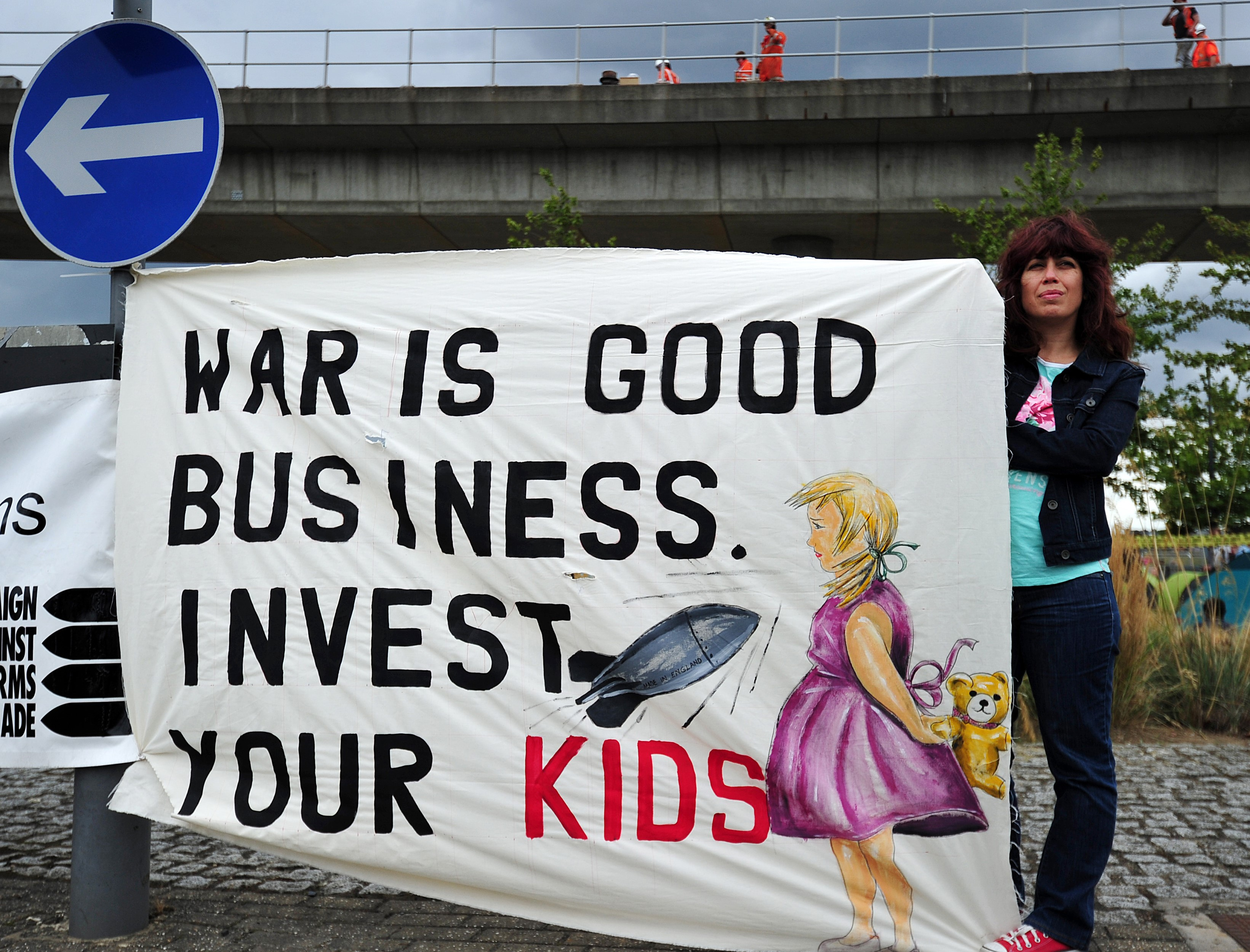 A protester holds a banner during a demonstration against the arms fair (AFP)