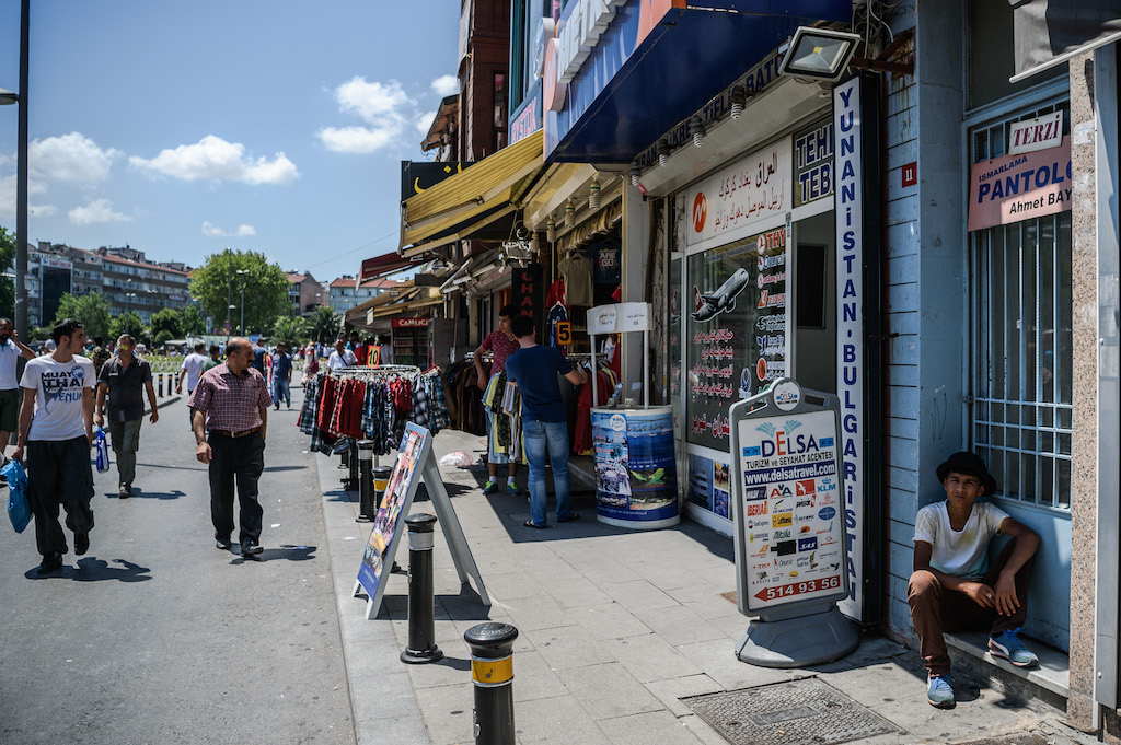 Syrian and Turkish people walk in a street next to shops with Arabic letters on July 4 ,2016 in Fatih neighbourhood in Istanbul (AFP)