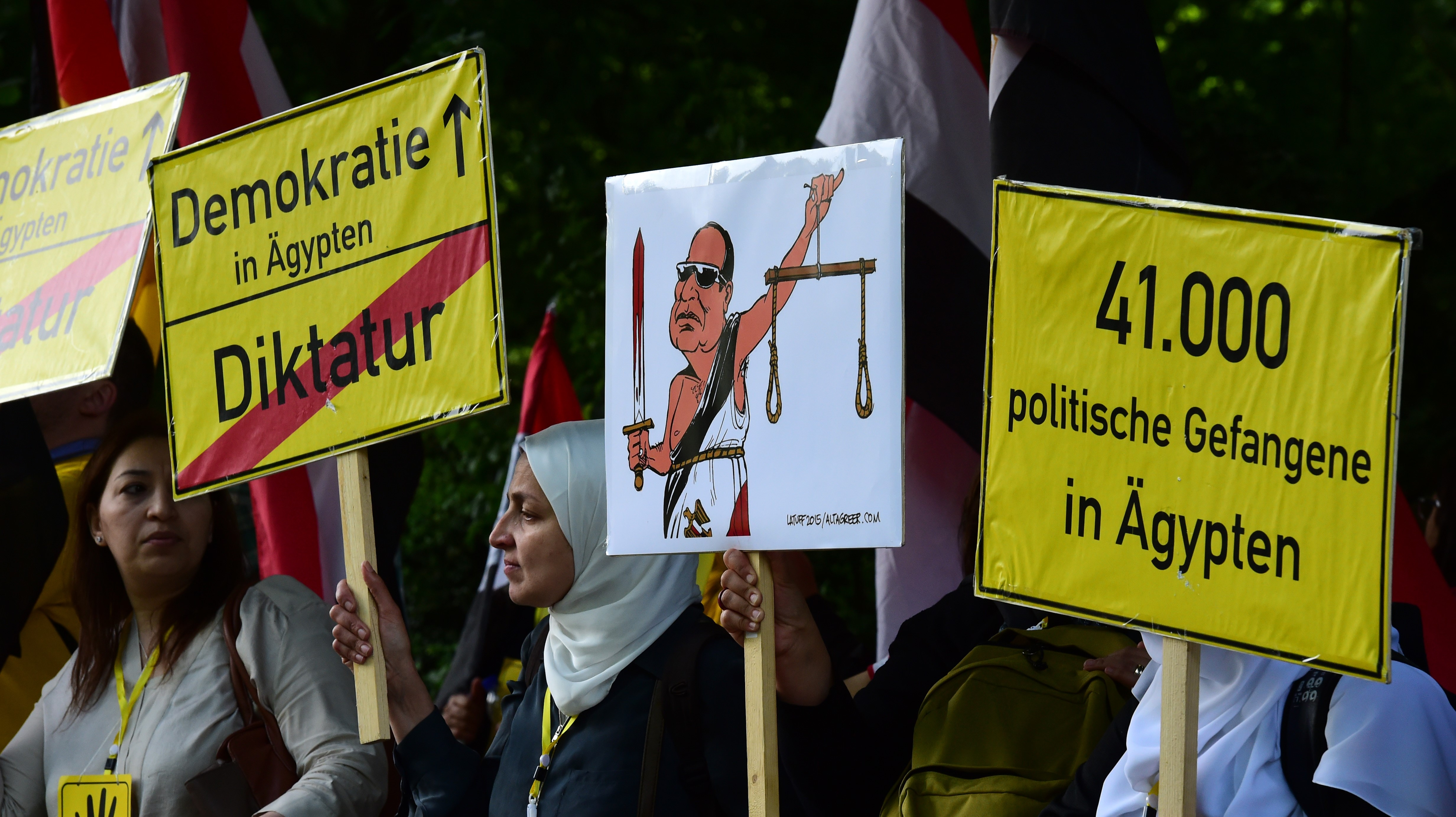 """Protesters hold banners reading """"Democracy in Egypt- Dictatorship"""" prior to Sisi's arrival for a meeting with the German president in Berlin in 2015 (AFP)"""