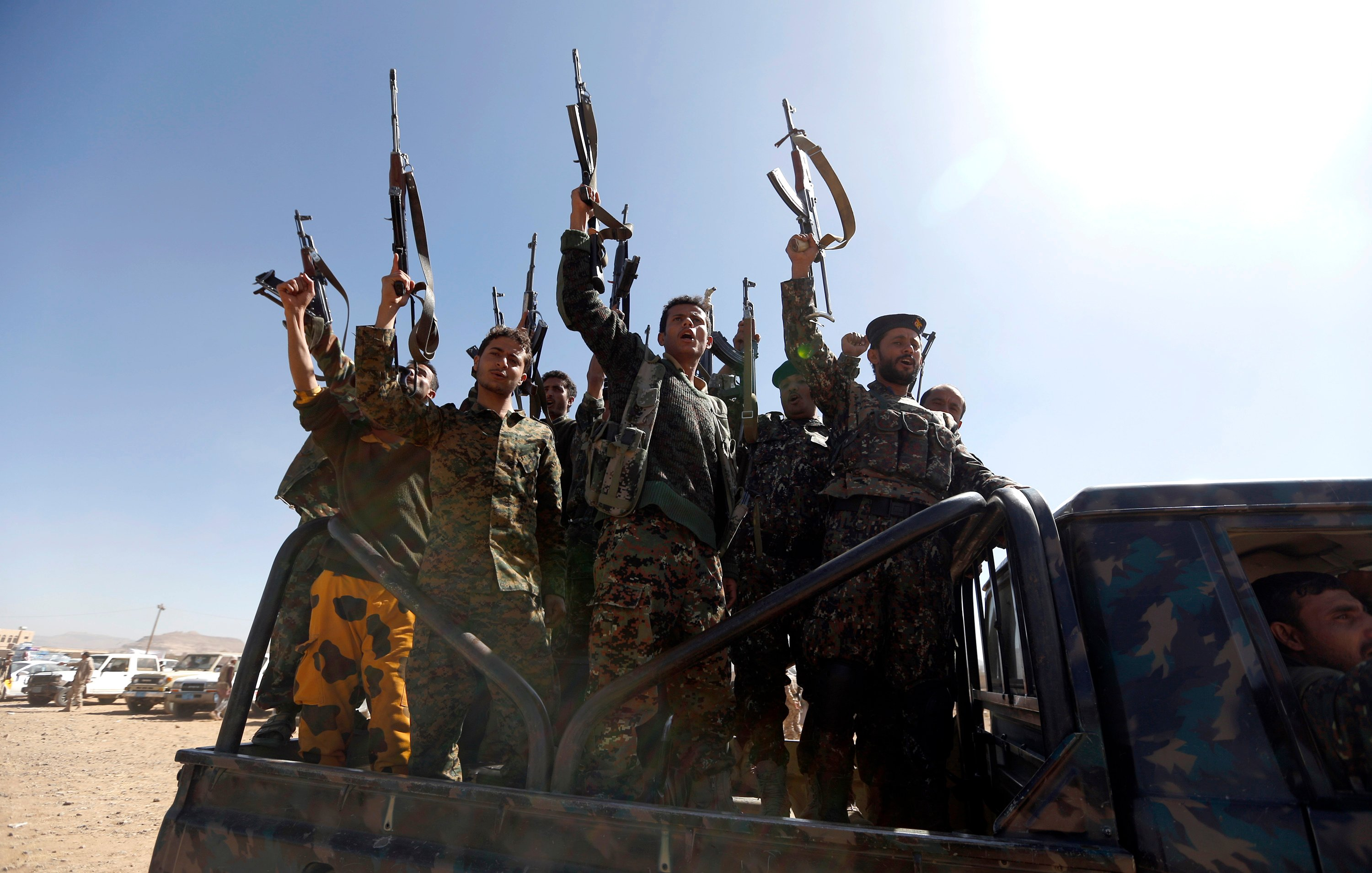 Newly recruited Houthi fighters chant slogans as they ride a military vehicle during a gathering in the capital Sanaa (AFP)