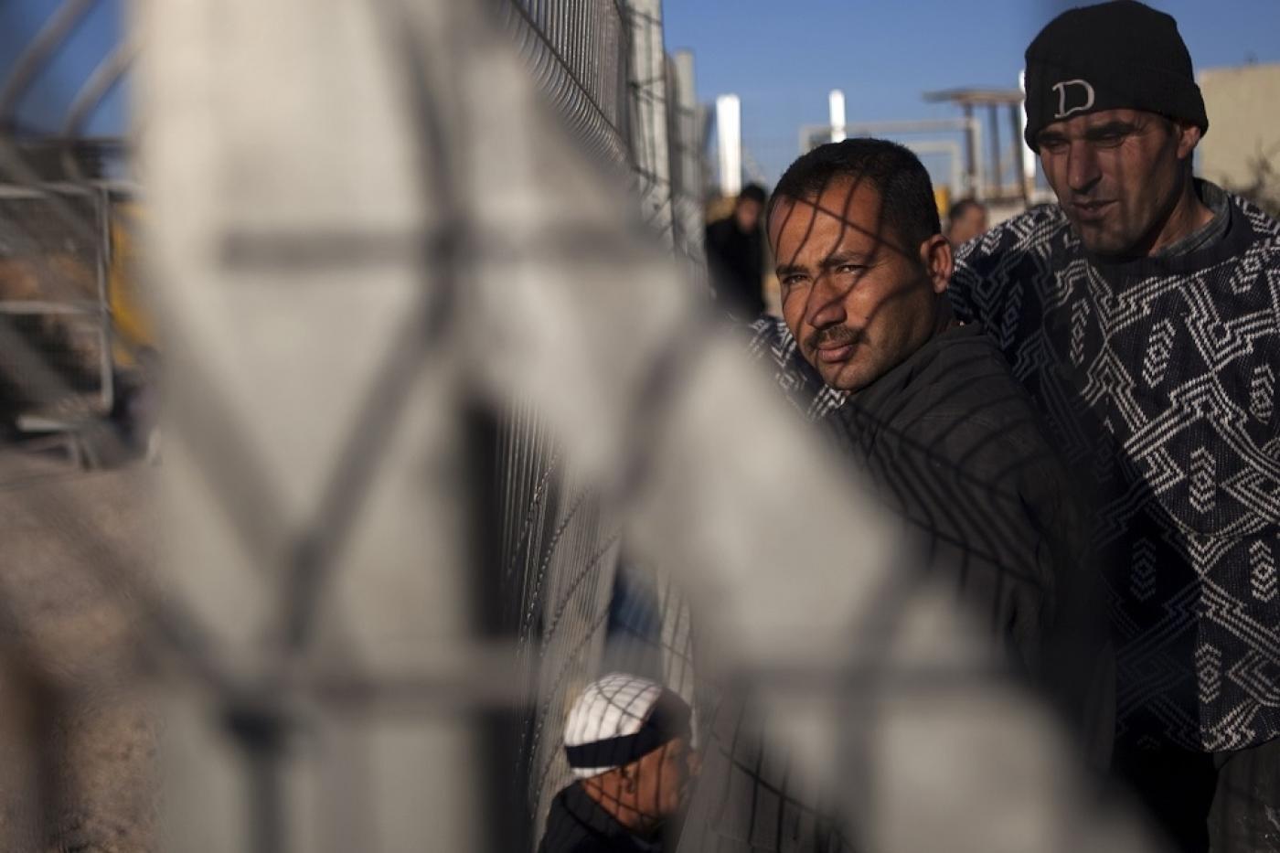 Des travailleurs palestiniens attendent l'ouverture d'un portail entre la colonie illégale de Modiin Illit et le village cisjordanien de Harbeta après leur journée de travail en Israël (AFP)