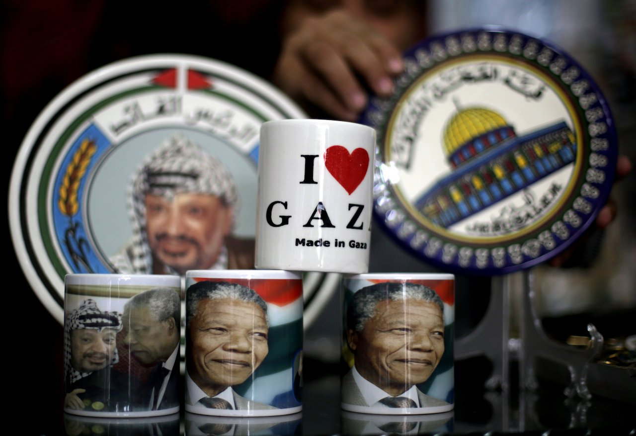 A vendor displays cups bearing the portrait of late South African former president Nelson Mandela and late Palestinian leader Yasser Arafat (L) in Gaza City (AFP)