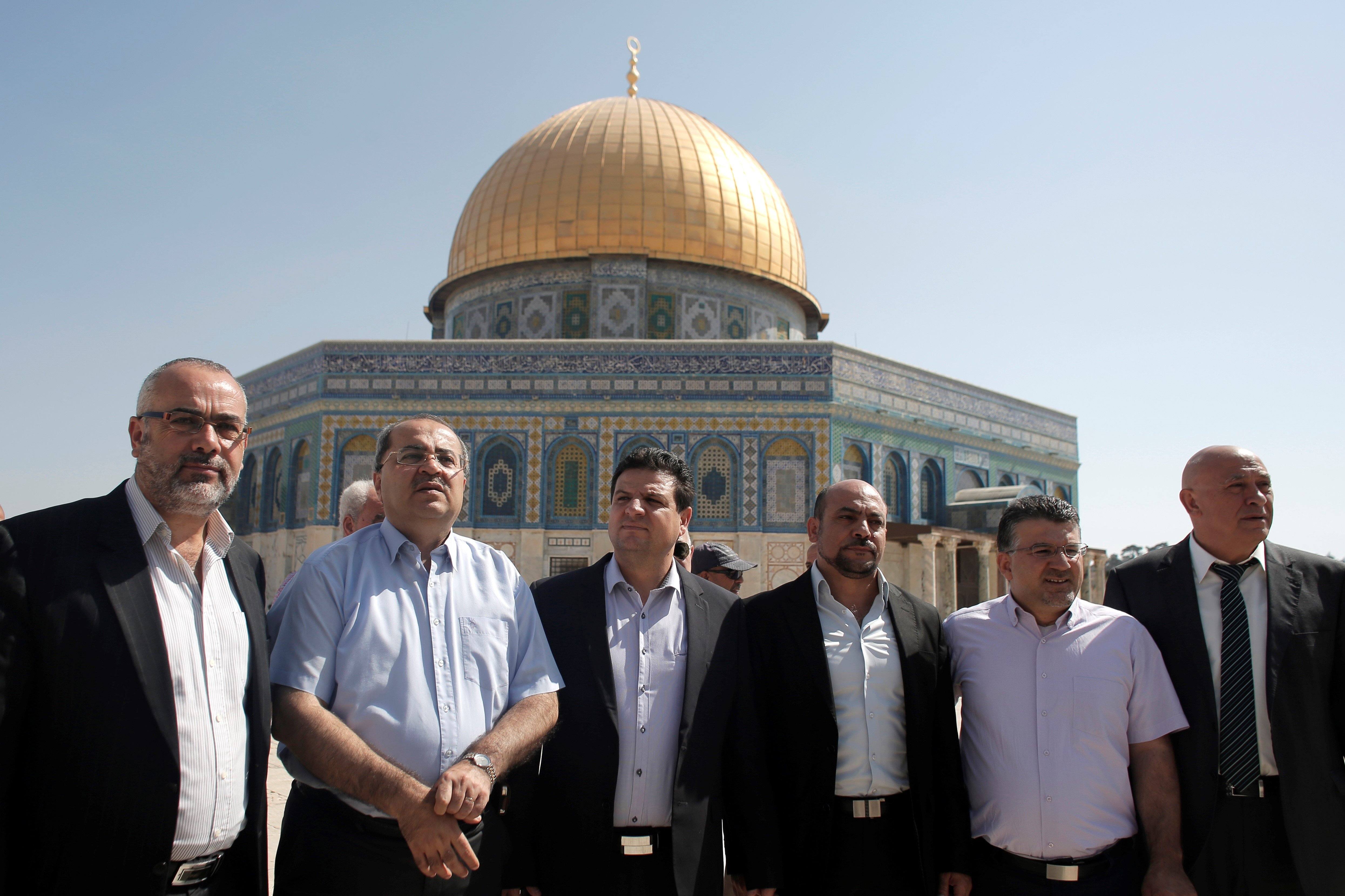 Members of the Joint List of Arab parties pose for a photo in front of the Dome of the Rock at the Al-Aqsa Mosque compound on 28 July, 2015 (AFP)