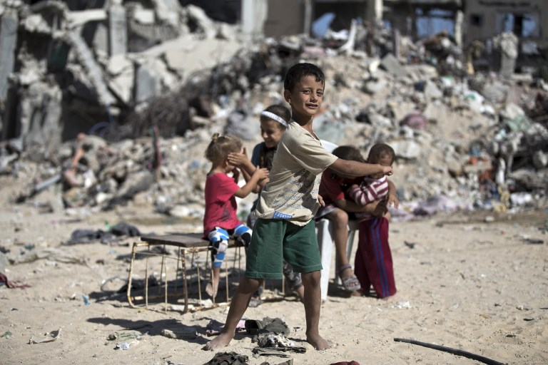 Palestinian children play next to the rubble of buildings destroyed in the 2014 Gaza war (AFP)