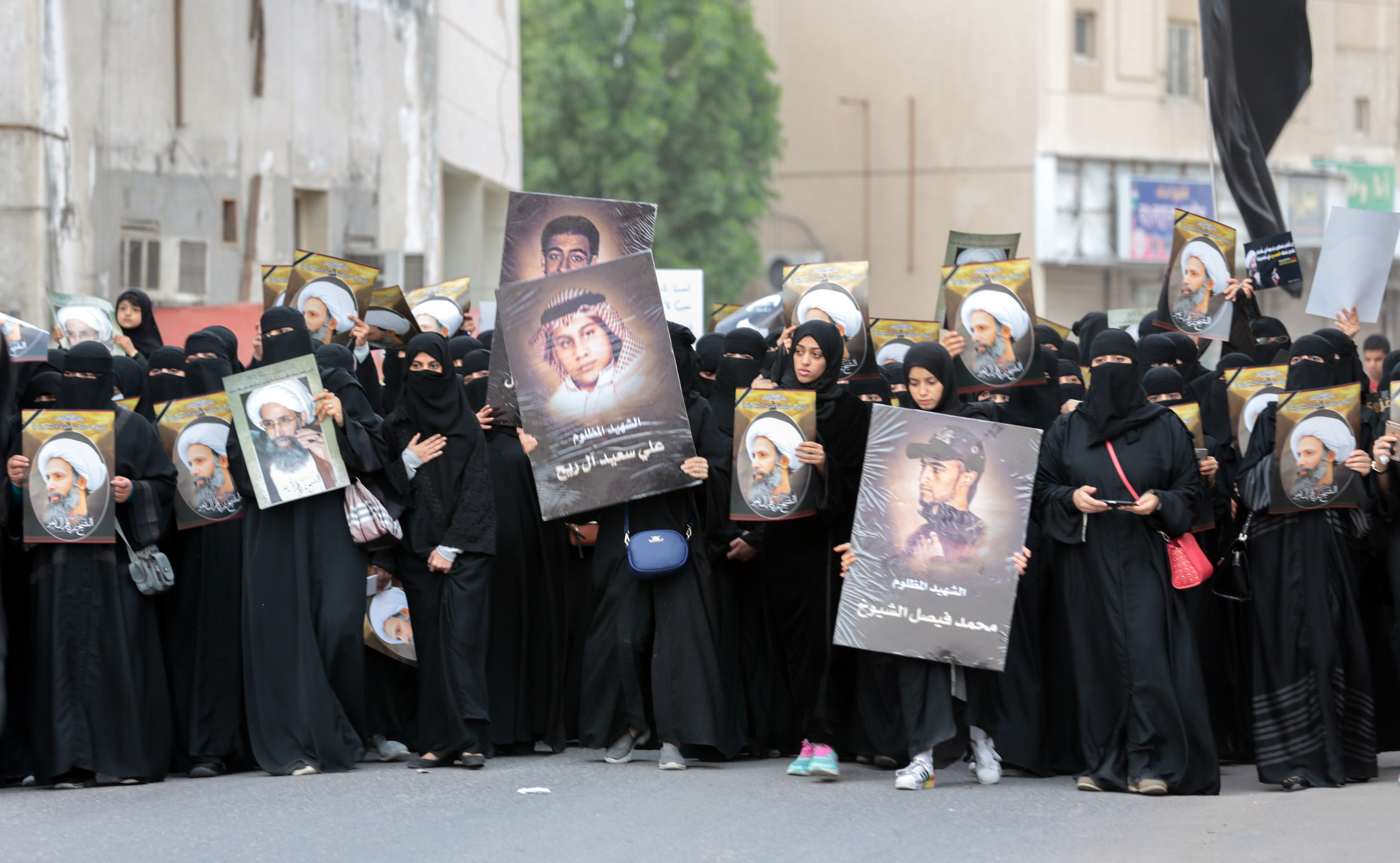 Saudi Shiite women hold placards bearing a portrait of prominent Shiite Muslim cleric Nimr al-Nimr during a protest on 8 January, 2016 in Qatif (AFP)