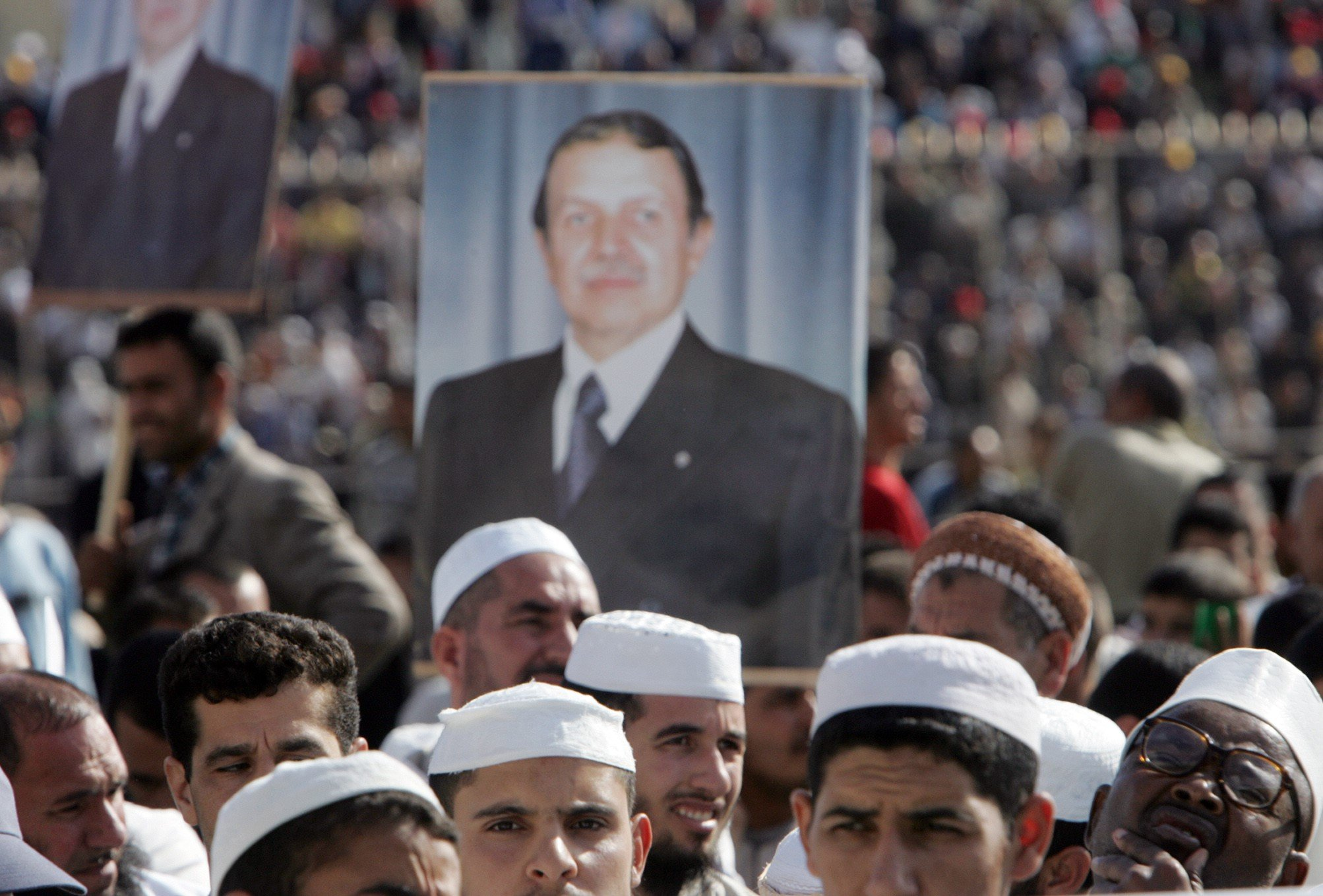 Islamist supporters of Bouteflika hold his portrait as they attend a rally in Tizi-Ouzou on 19 September 2005 (AFP)