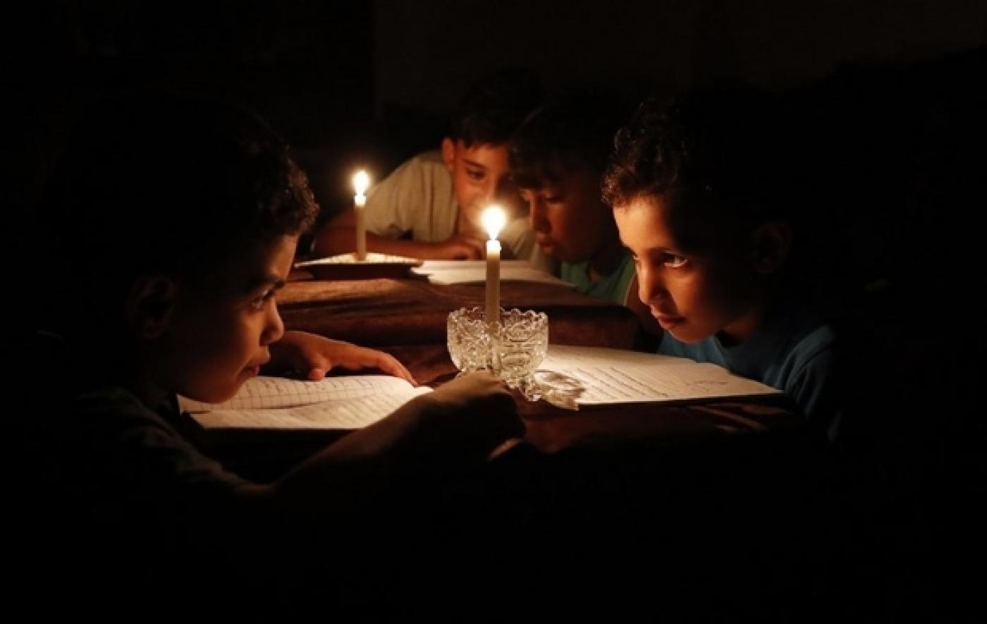 Des enfants palestiniens lisent des livres chez eux à la lueur de bougies en raison des pénuries d'électricité à Gaza, en juin2017 (AFP)
