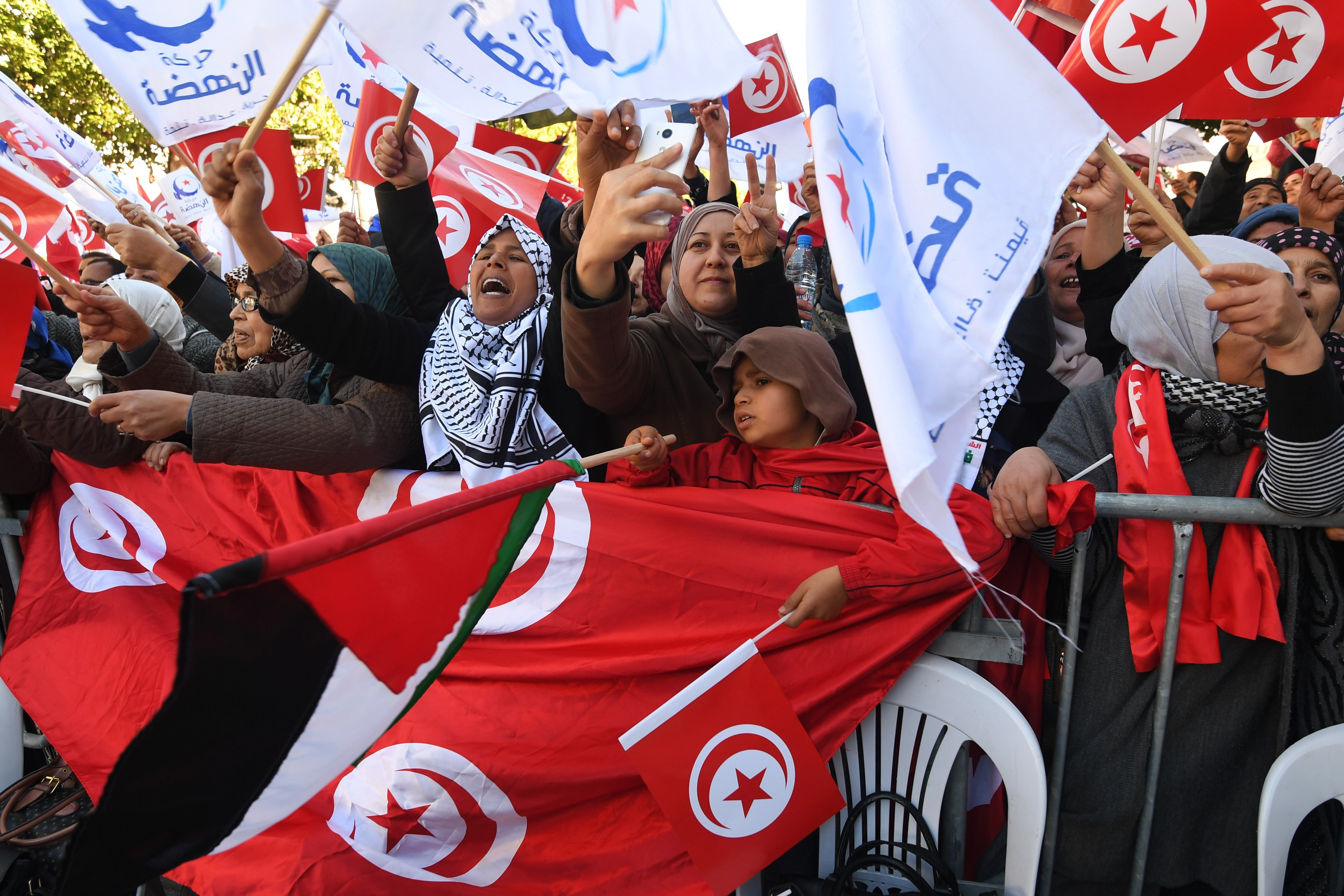 Tunisians wave national flag as they gather on 14 January, 2018 to mark the seven year anniversary since the uprising that launched the Arab Spring (AFP)