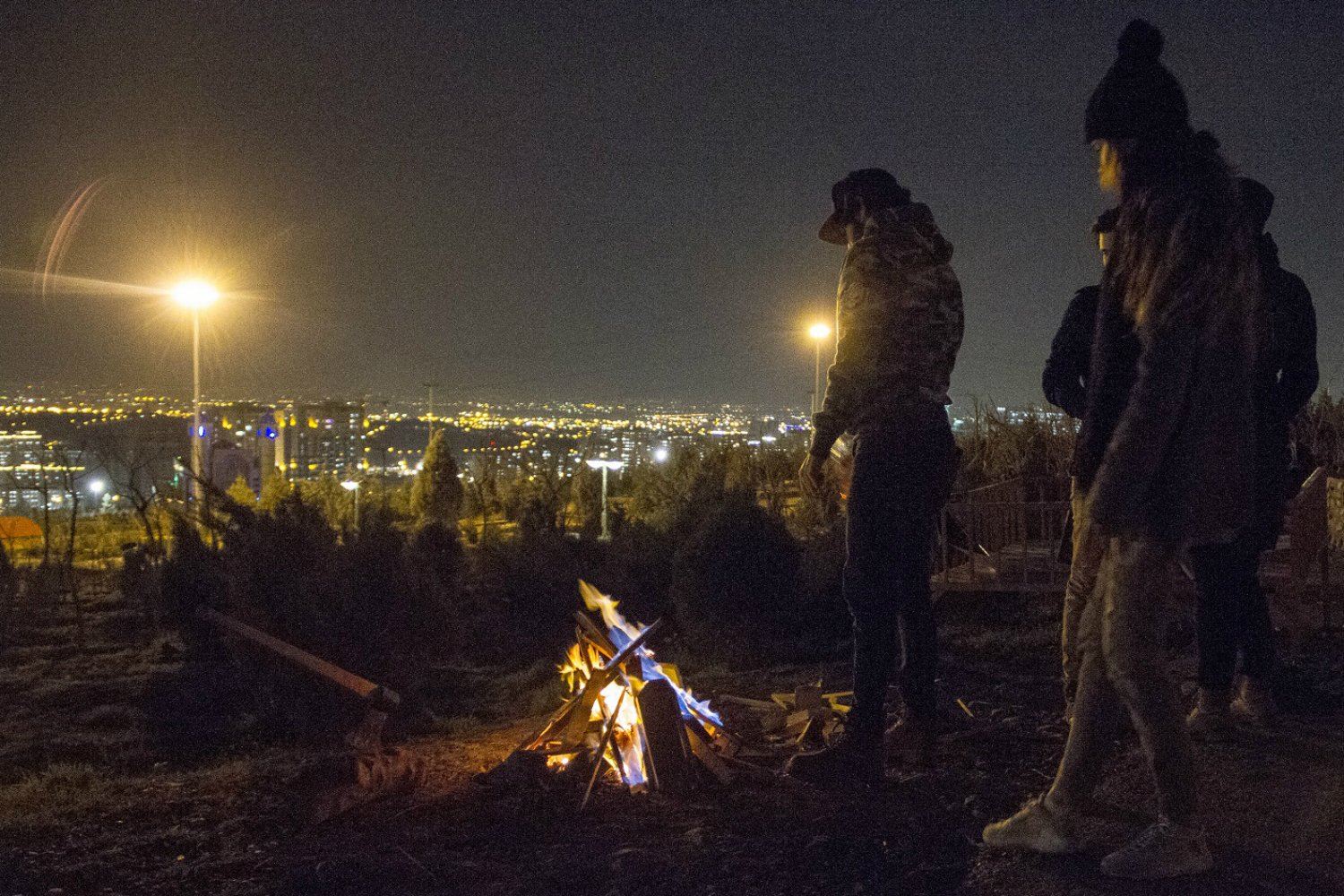 In the north-west in Abshar, at the foot of the mountains, small groups of young men and women hang around campfires near the Tehran Waterfall Park. (MEE)