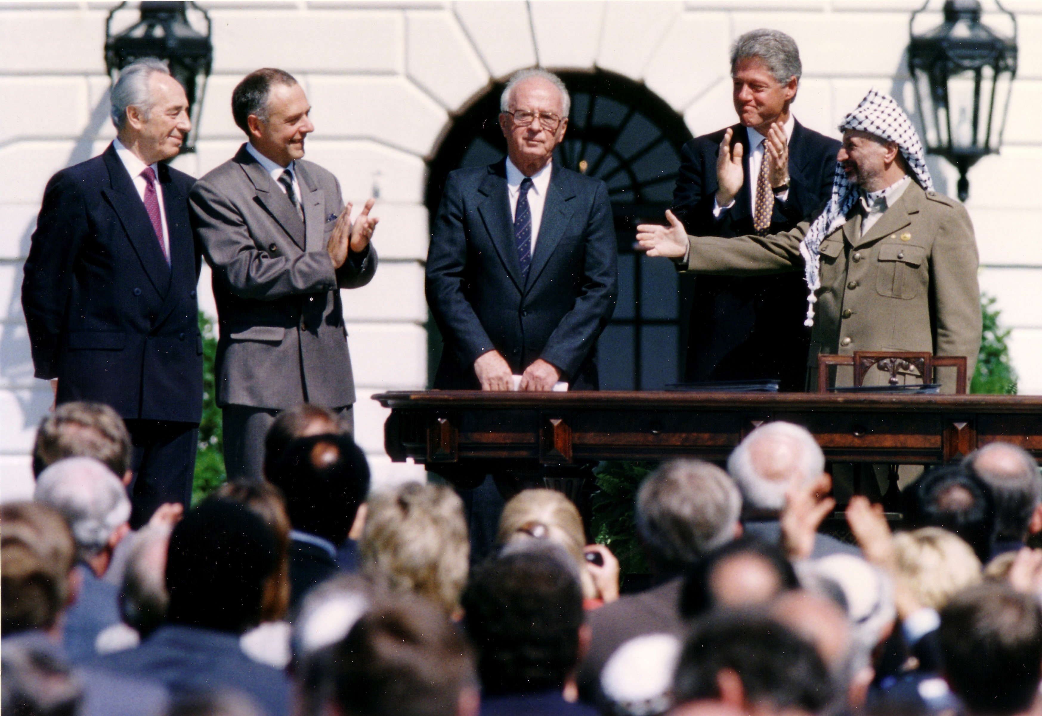 PLO Chairman Yasser Arafat (R) gestures to Israeli Prime Minister Yitzhak Rabin (3rd R), as US President Bill Clinton (2nd R) stands between them at the White House on 13 September, 1993 (Reuters)
