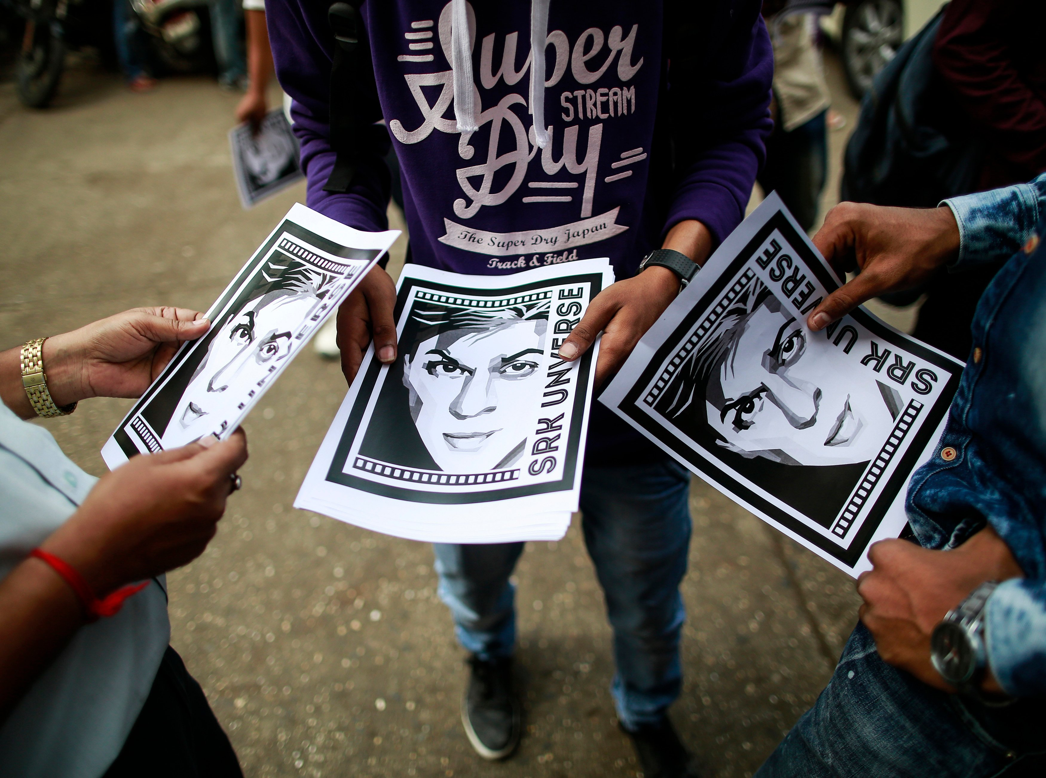 Cinema goers hold posters of actor Shah Rukh Khan (Reuters)
