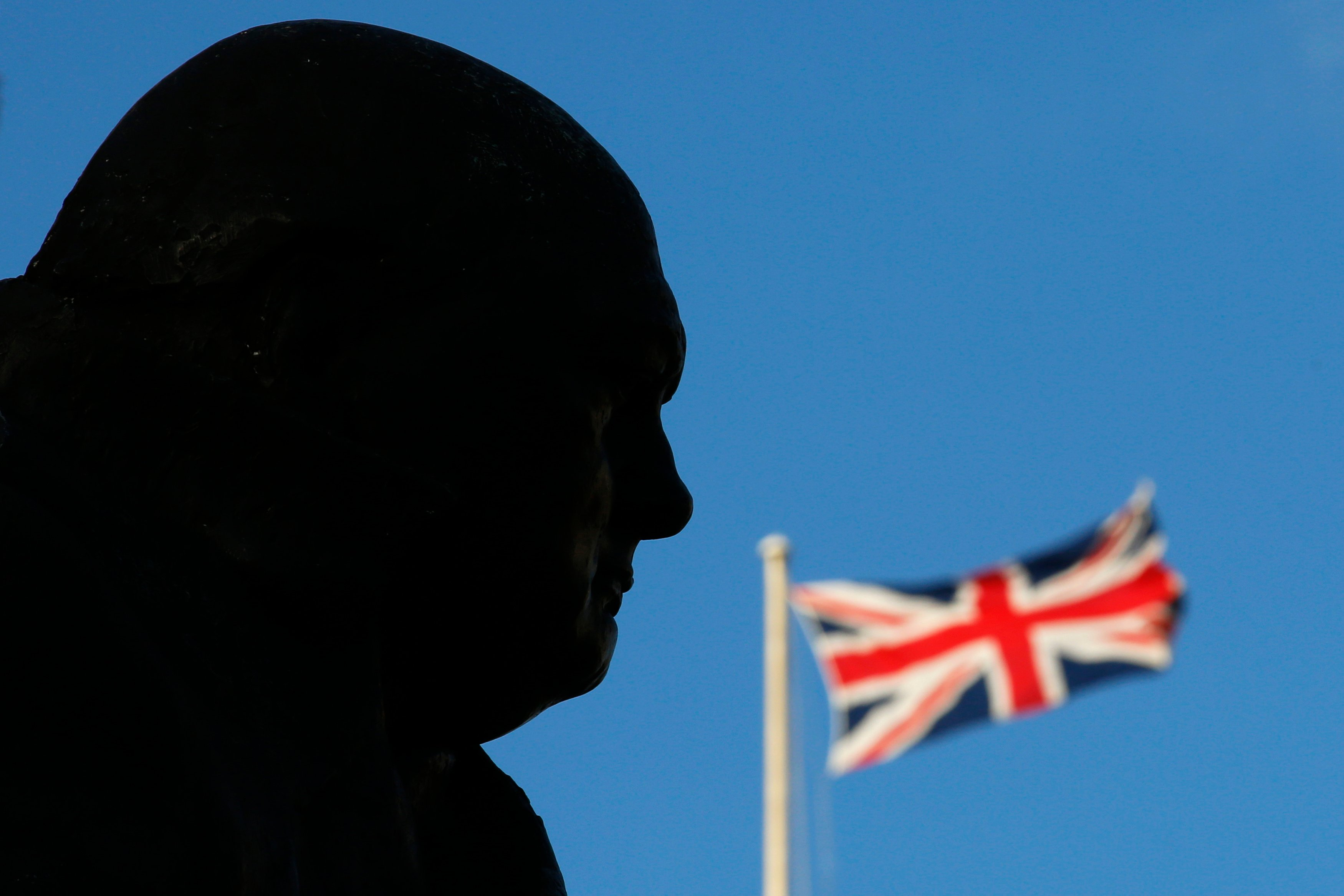 A Union Flag is seen behind a statue of Britain's former Prime Minister Winston Churchill in London