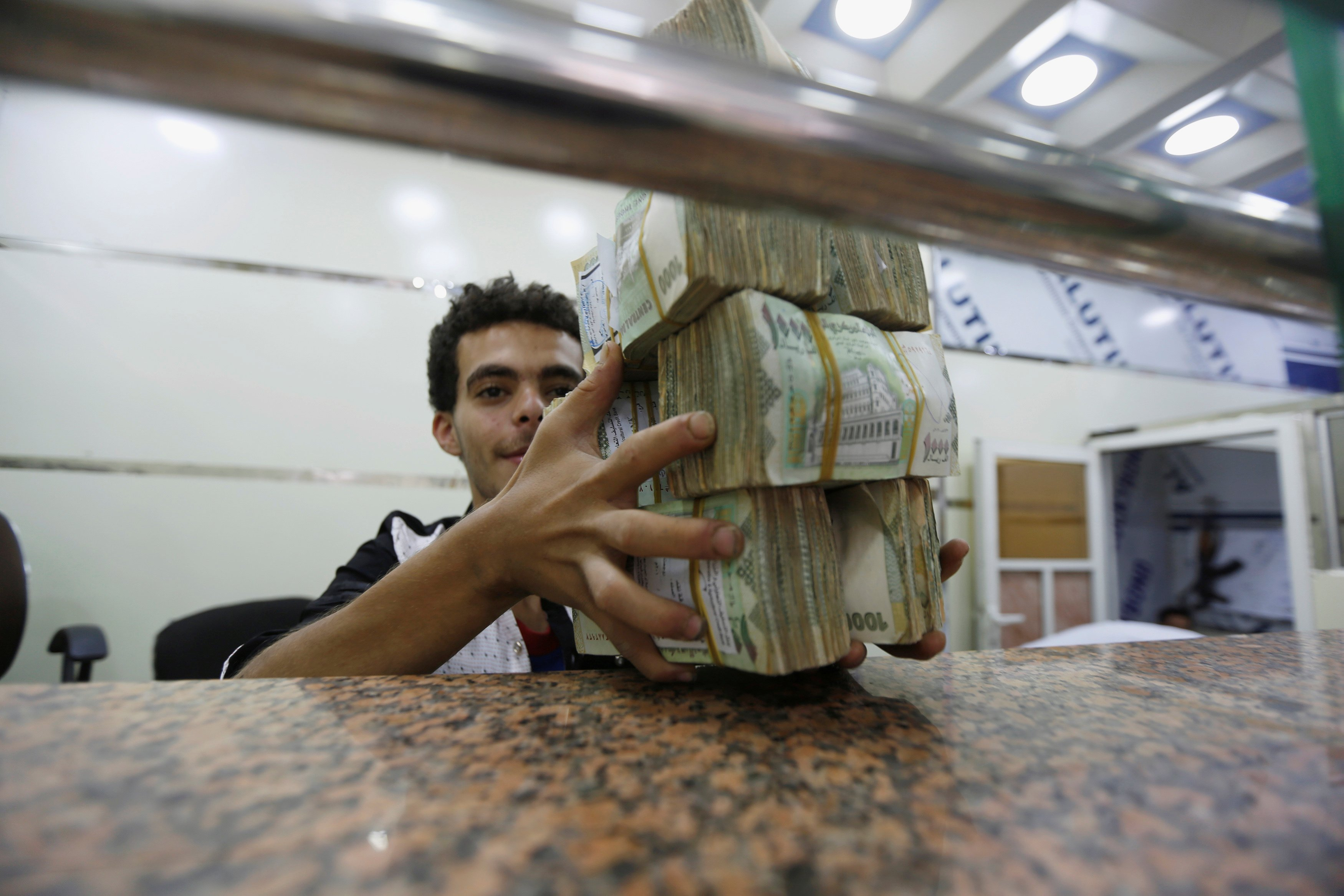 A money changer holds bundles of Yemeni currency at an exchange shop in Sanaa (Reuters)