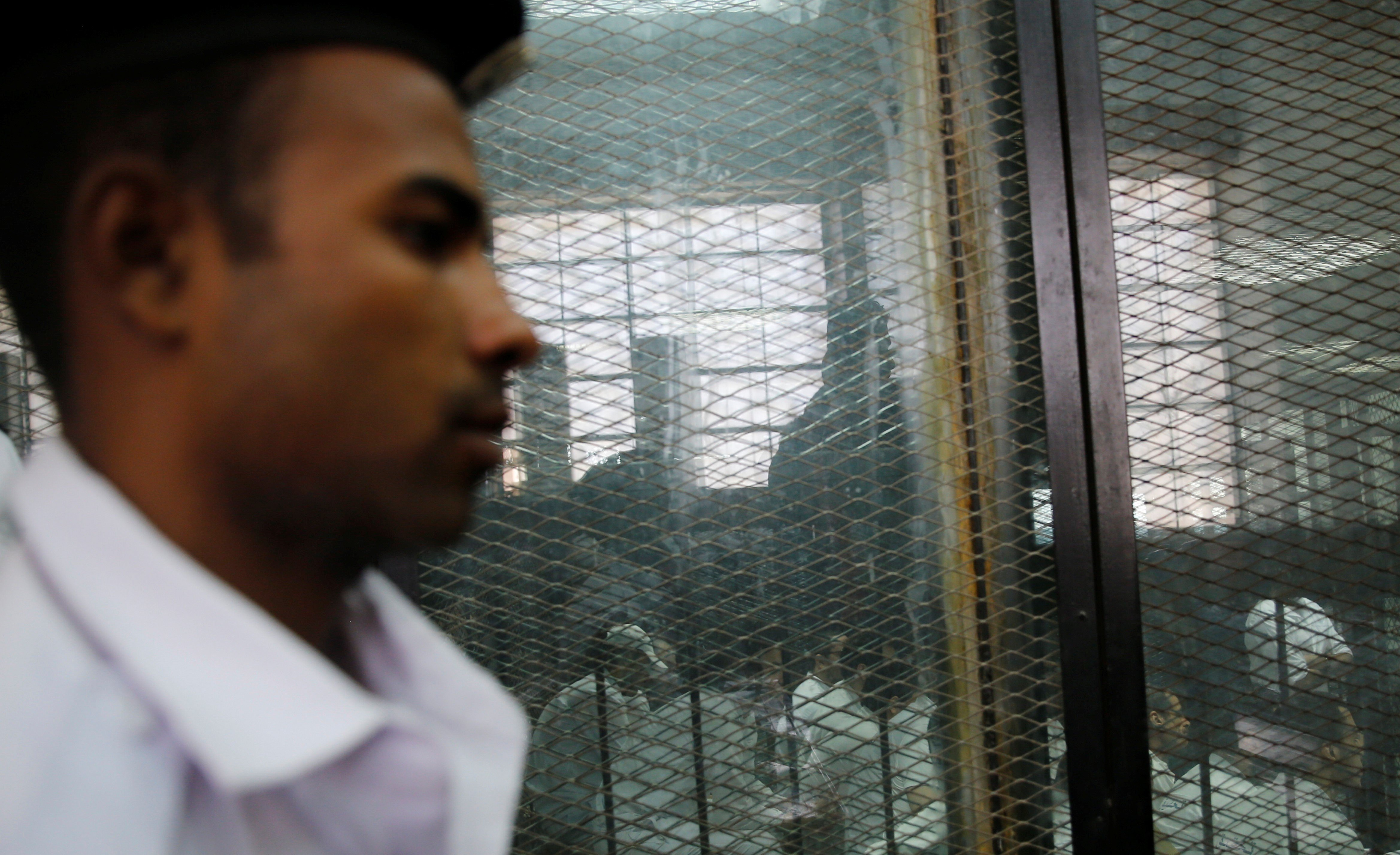 A police officer stands guard as defendants accused of involvement in the 2015 assassination of Egypt's top prosecutor on 17 June, 2015 (Reuters)