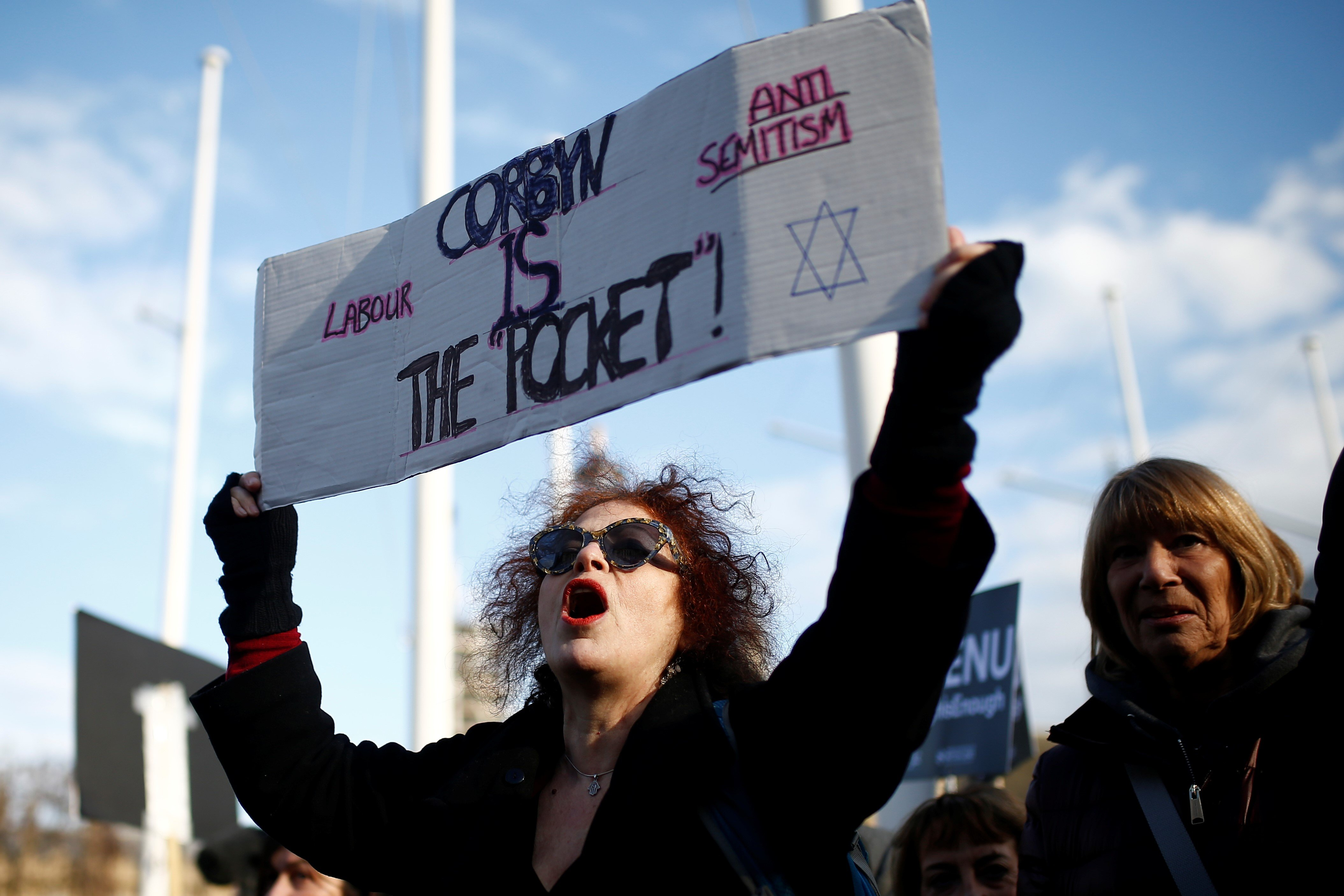 Protesters hold placards and flags during a demonstration, organised by the British Board of Jewish Deputies for those who oppose anti-Semitism, in Parliament Square in London, Britain, March 26, 2018