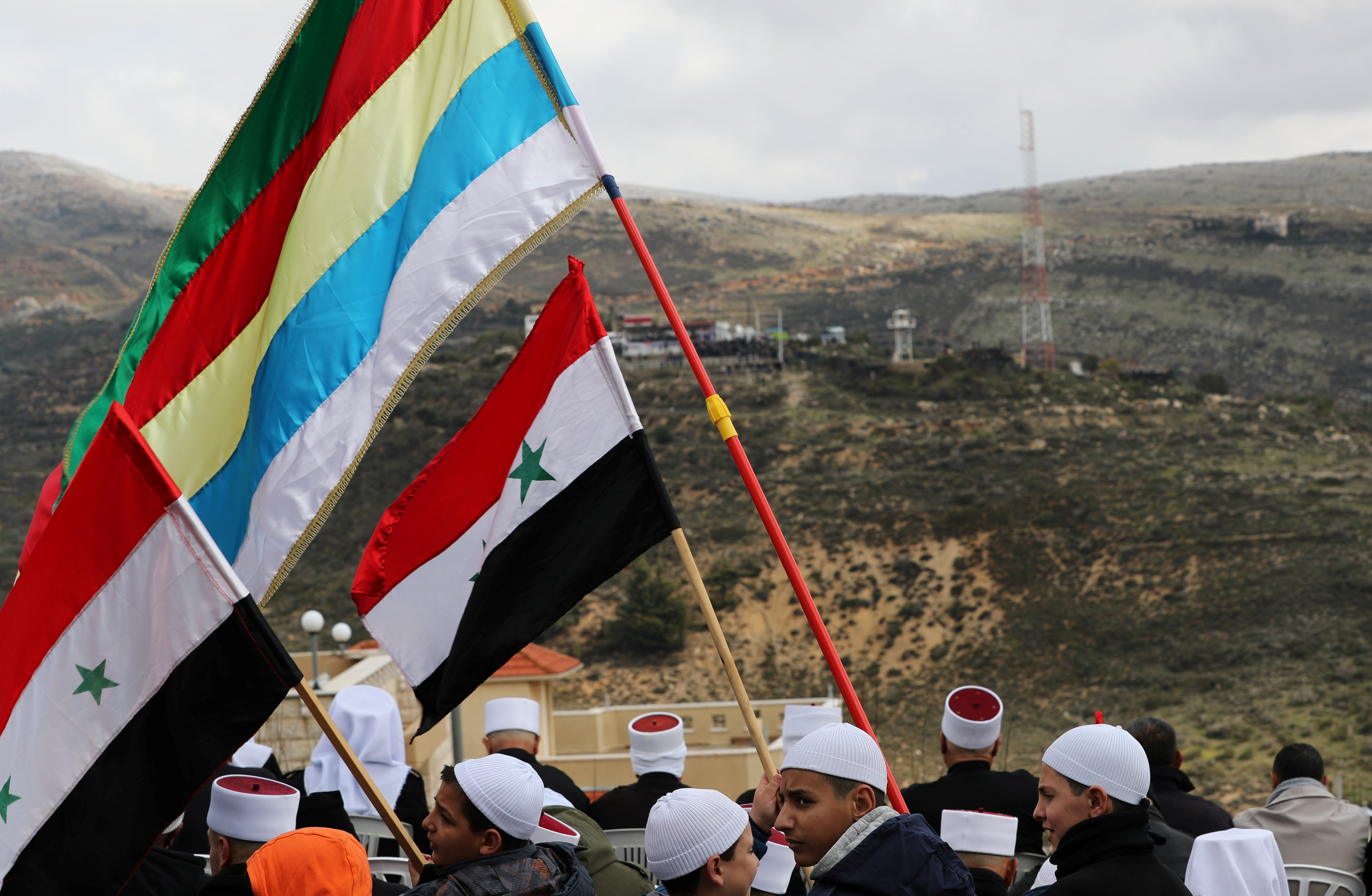 Members of the Druze community holds Syrian and Druze flags during a rally marking the anniversary of Israel's annexation of the Golan Heights on 14 February (REUTERS)