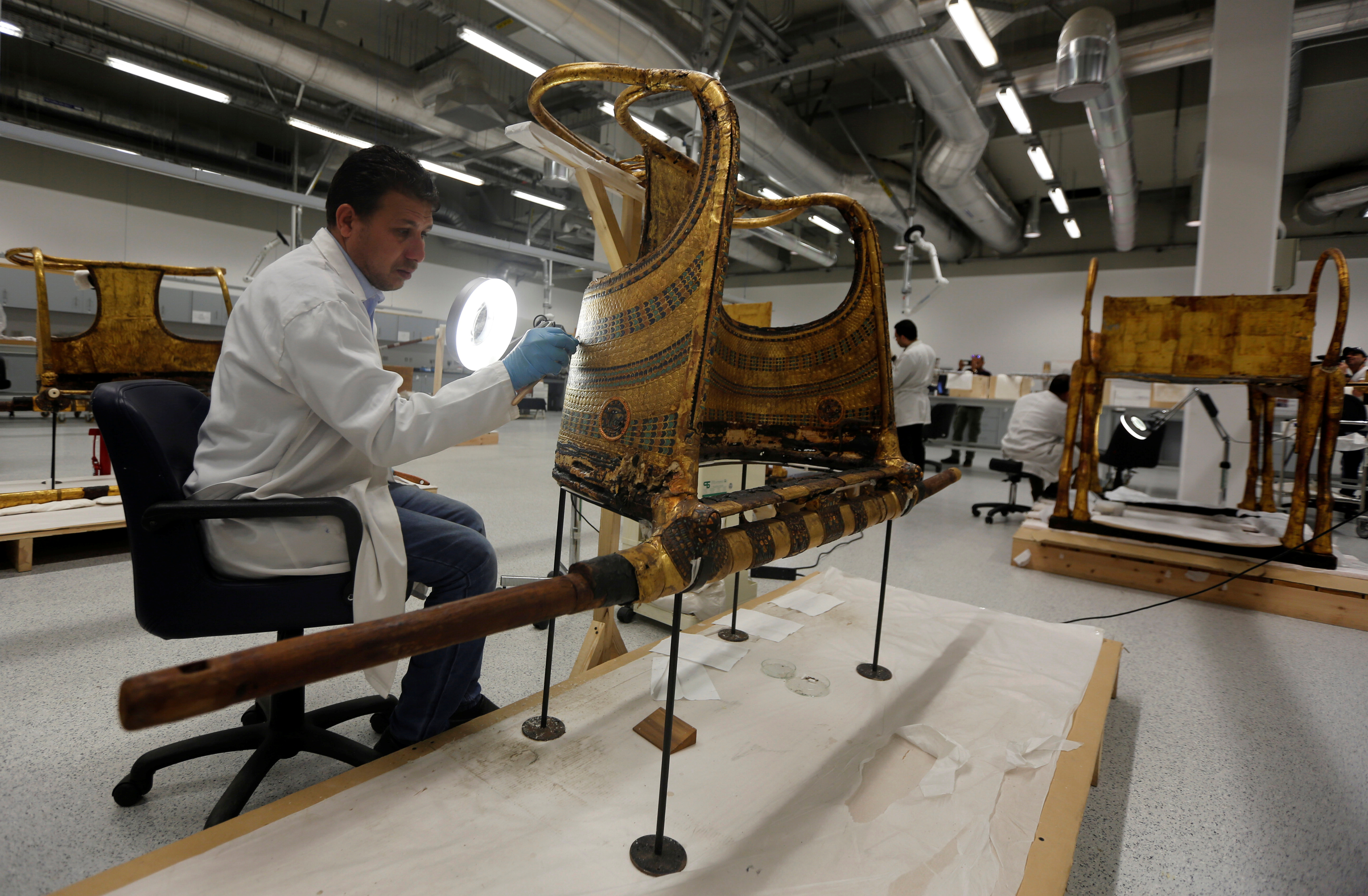 Here, an Egyptian archaeological technician renovates the golden war wheel which belonged to Tutankhamun: other treasures visible in the background include a gold pharonic bed to the right (Reuters)