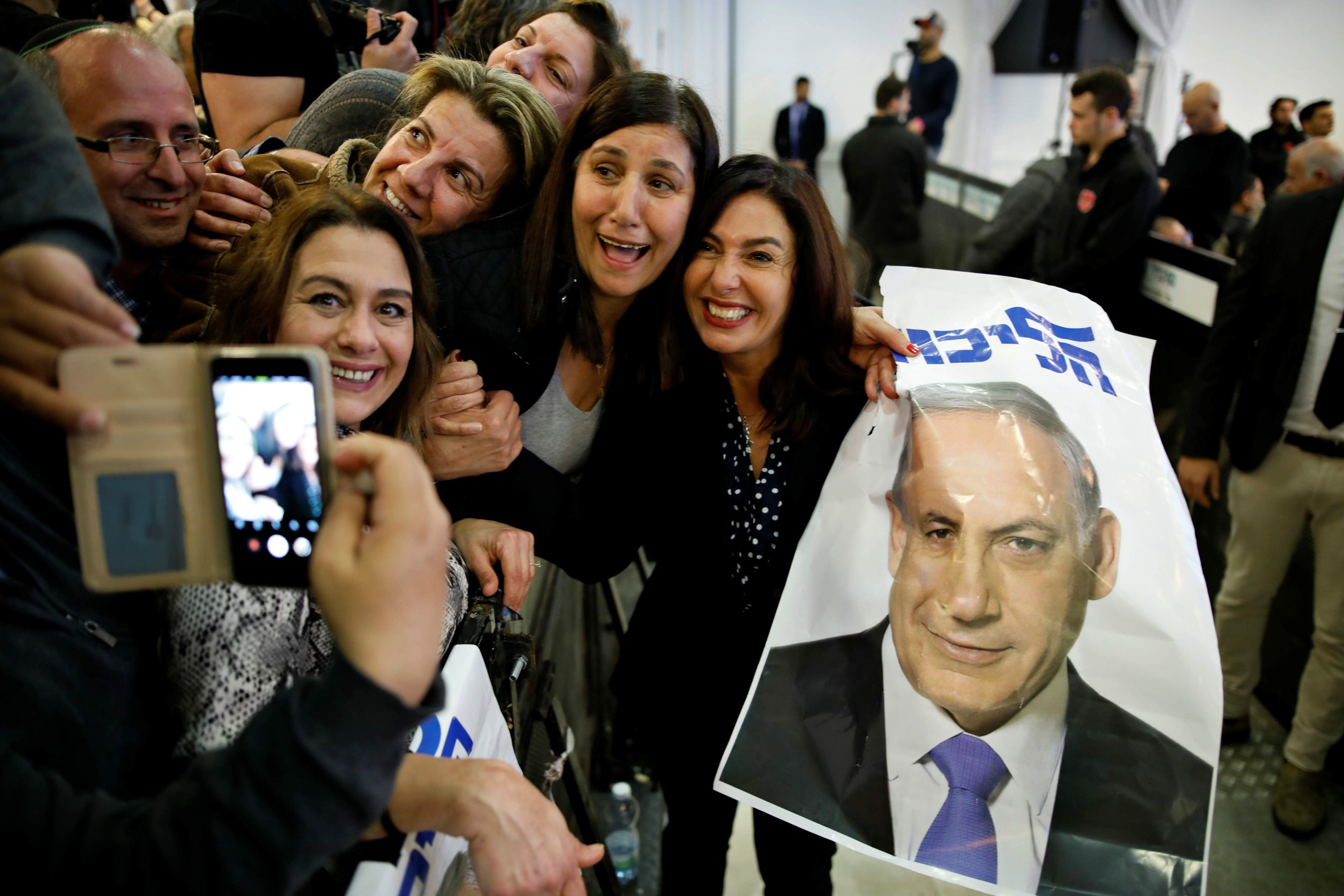 Israel's Minister of Culture and Sport Miri Regev and supporters of the Likud Party hold a photo of Israeli Prime Minister Benjamin Netanyahu at the launch of Likud party's election campaign (Reuters)