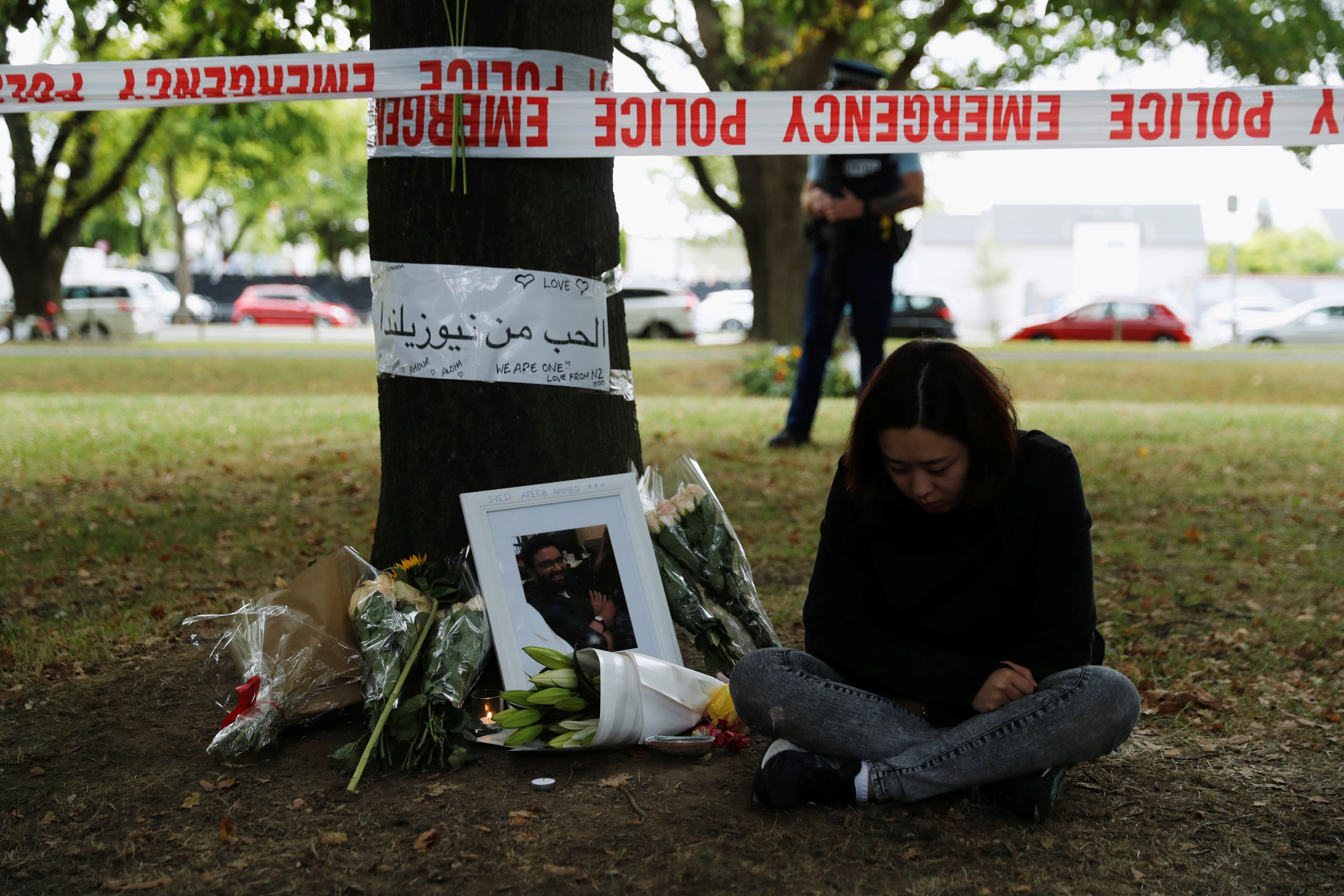 A woman sits next to flowers and messages displayed at a memorial site for victims of Friday's shooting, in front of the Masjid Al Noor mosque in Christchurch, New Zealand 18 March, 2019 (REUTERS)