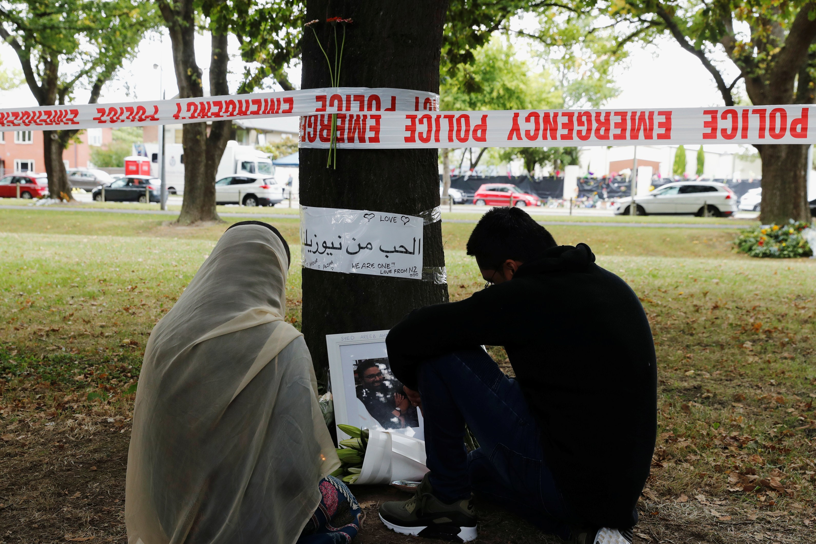People visit at a memorial site for victims of Friday's shooting, in front of the Masjid Al Noor mosque in Christchurch, New Zealand on 18 March (Reuters)