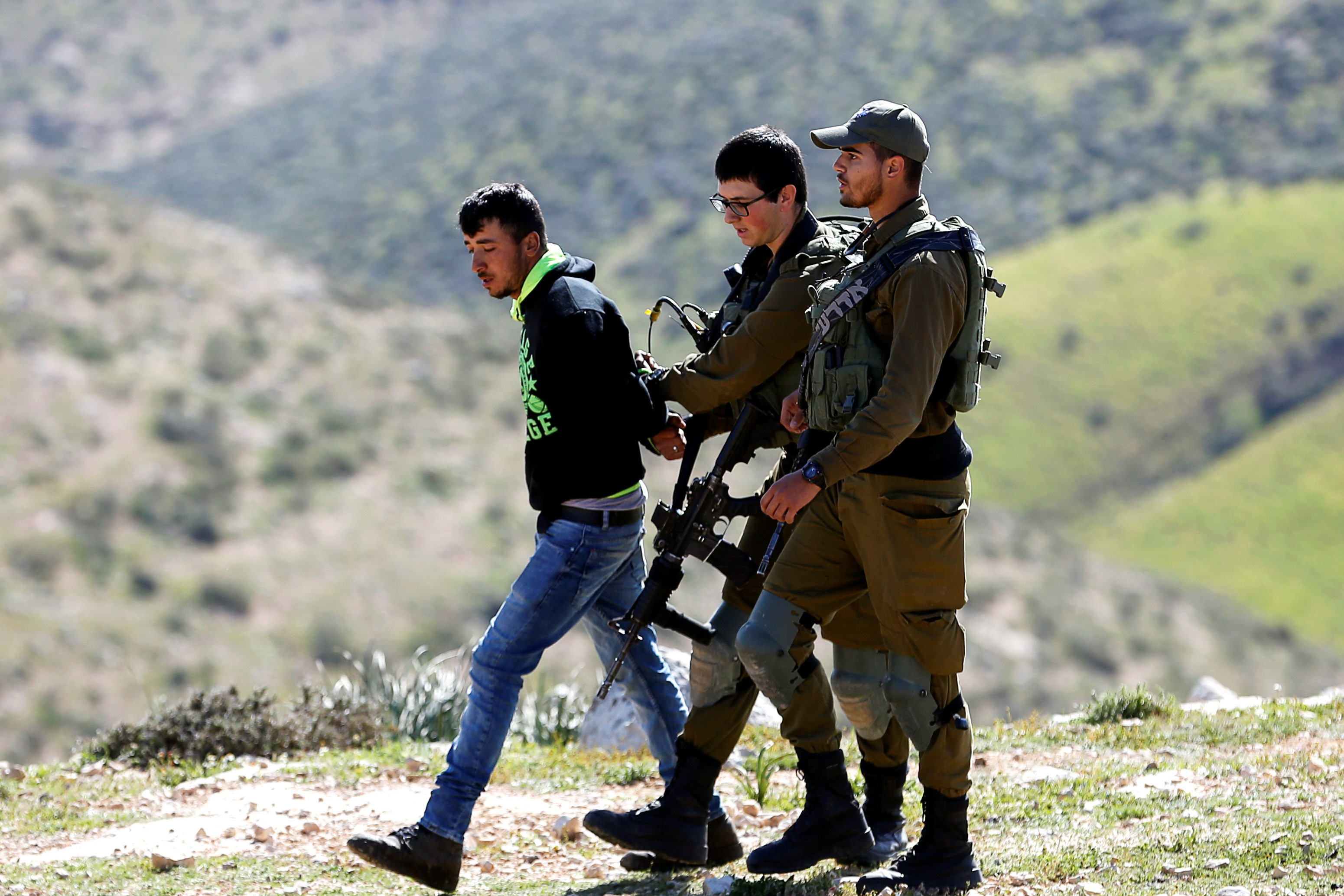 Israeli soldiers detain a Palestinian during the demolishing of his house that army told them they didn't obtain a construction license, near Yatta in the Israeli-occupied West Bank on 20 March (Reuters)