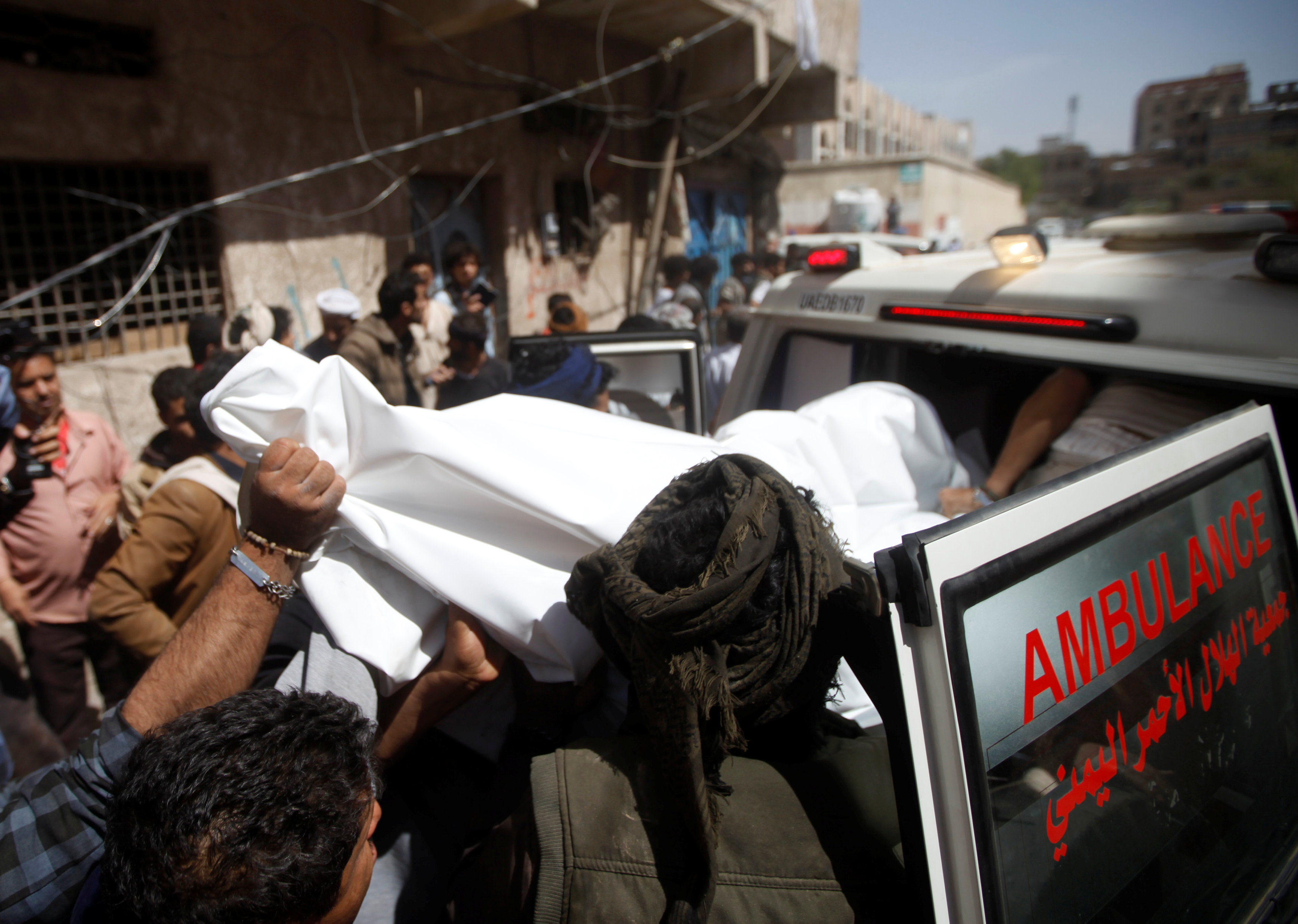 Yemeni men carry the body of a dead woman, who was killed by Saudi-led air strike in Sanaa