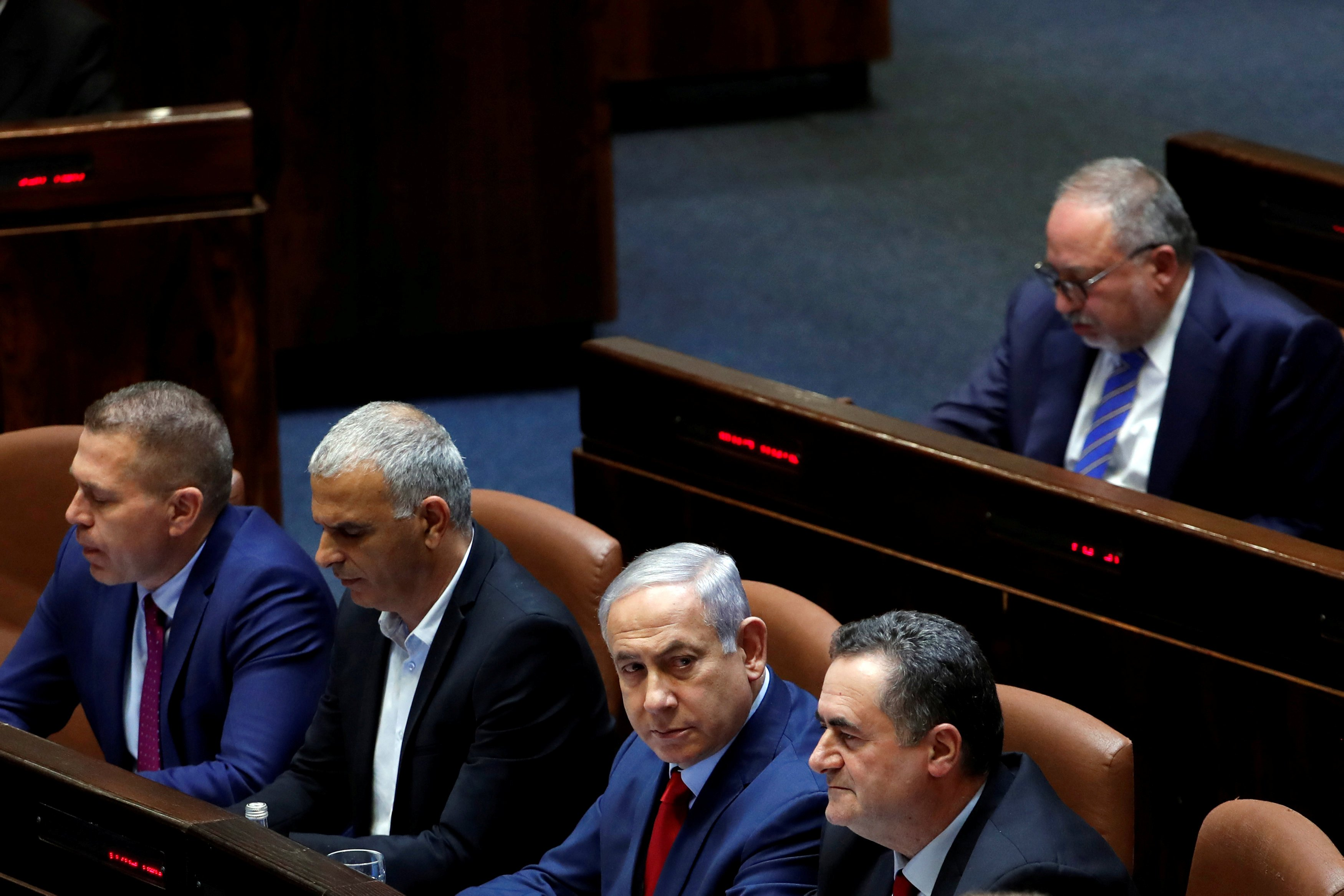 Israeli Prime Minister Benjamin Netanyahu sits with his ministers and Israel's former defence minister Avigdor Lieberman at the plenum at the Knesset, Israel's parliament (Reuters)