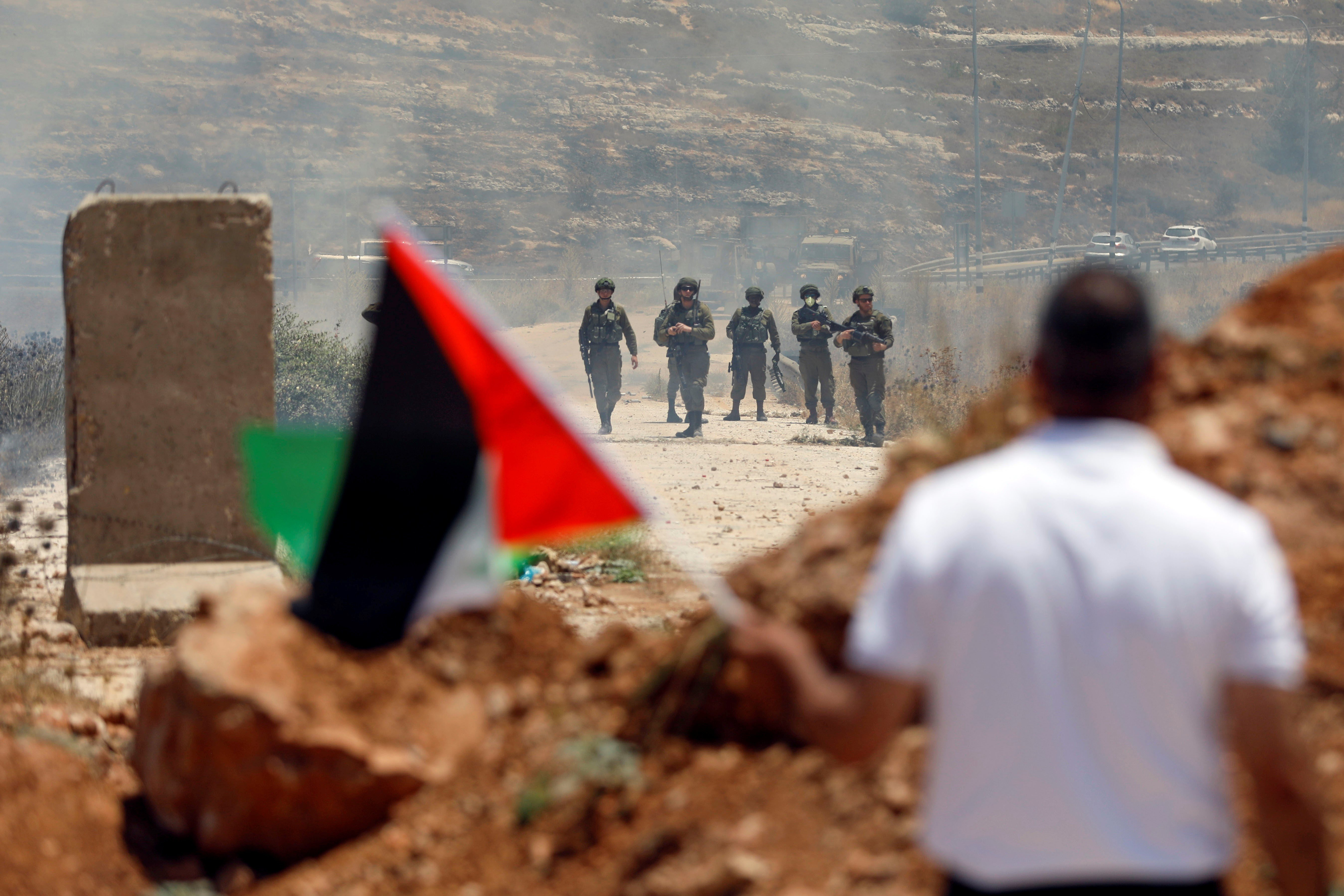 A demonstrator waves a Palestinian flag in front of Israeli forces in the Israeli-occupied West Bank on 25 June (Reuters)