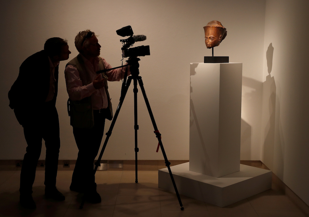 A camera crew films an Egyptian brown quartzite head of the God Amen which will be sold at auction at Christie's in London (Reuters)