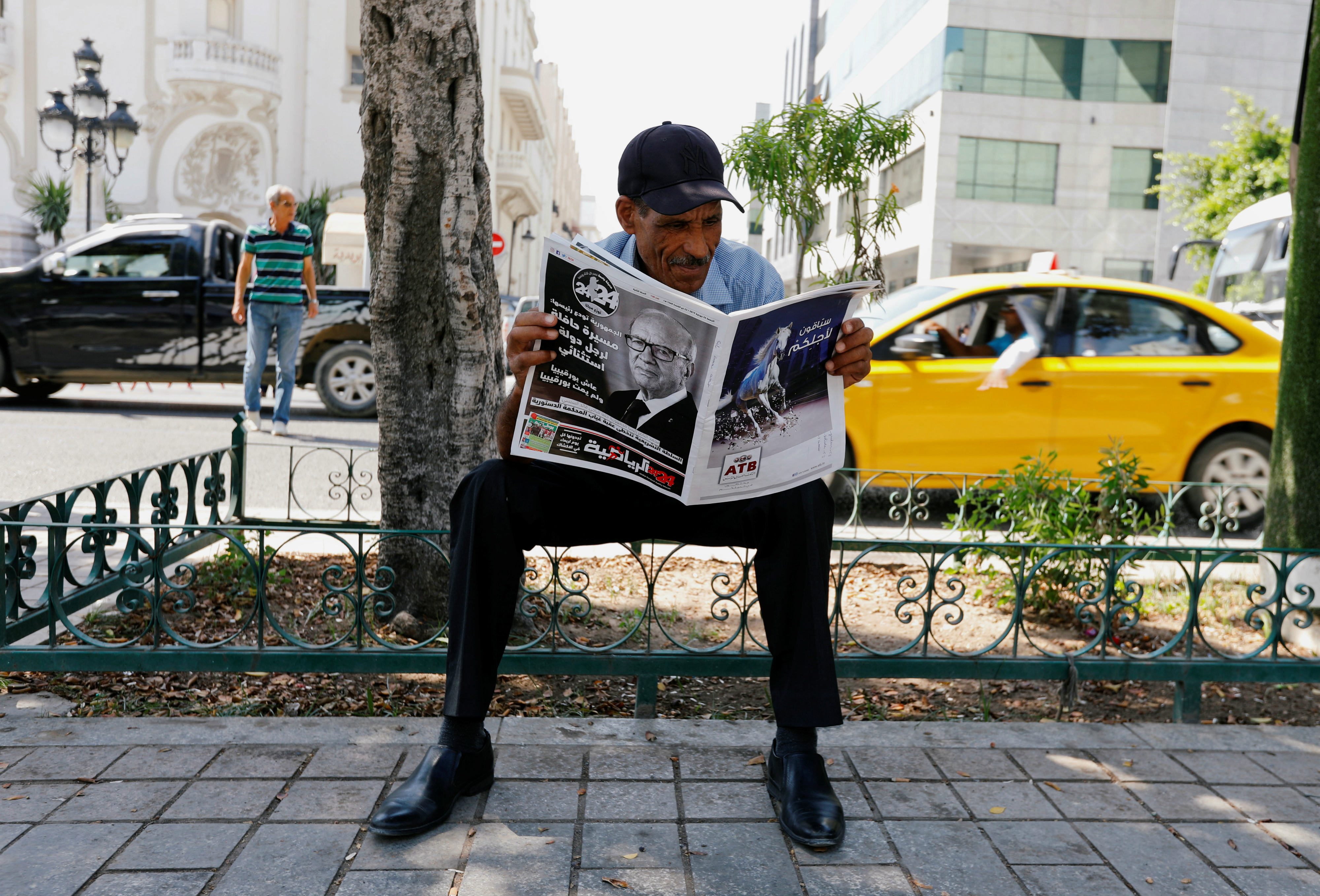 A man reads a local newspaper, displaying a picture of the late Tunisian President Beji Caid Essebsi in Tunis (Reuters)