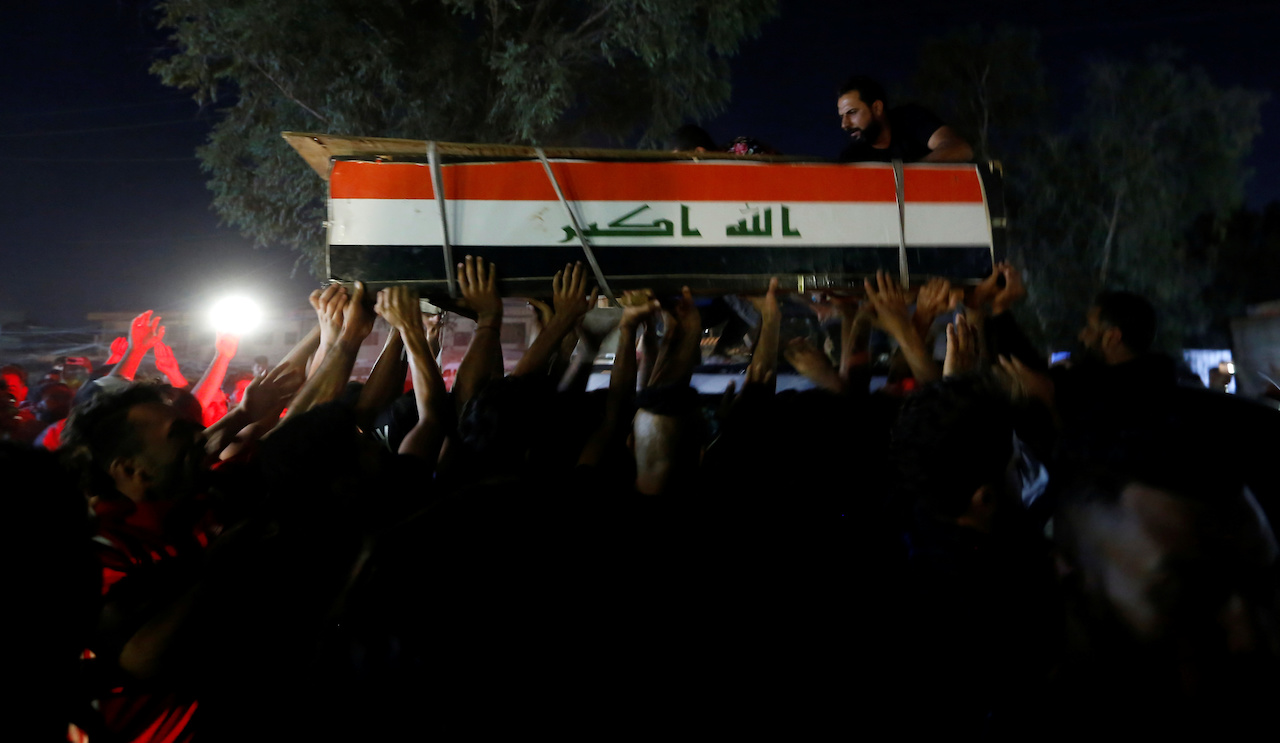 Men carry the coffin of a demonstrator who was killed during anti-government protests in Baghdad (Reuters)
