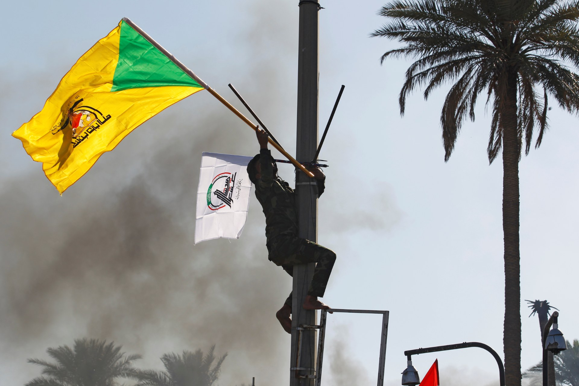 A member of Hashd al-Shaabi paramilitary forces holds a flag of Kataeb Hezbollah militia group during a protest to condemn air strikes on their bases, in Baghdad in December (Reuters)