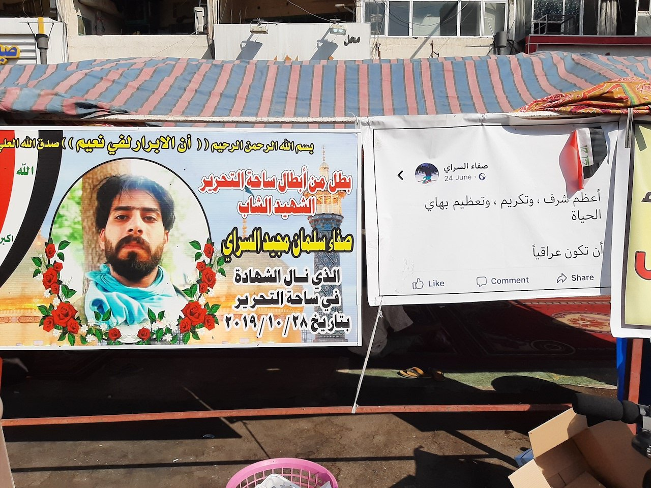 "A banner showing a Facebook picture of Safaa al-Sarray. Banner on left: ""The greatest honour and magnificence in this life is to be Iraqi"" (Alex MacDonald)"