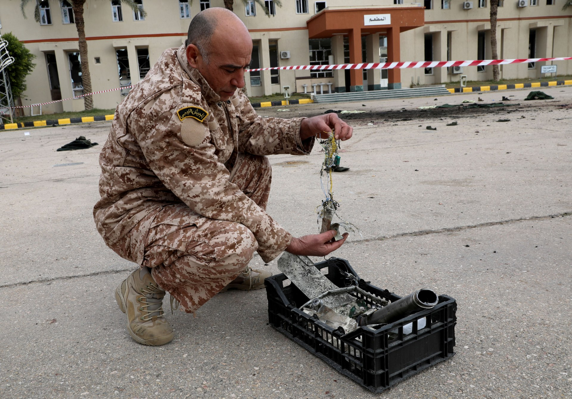 A GNA soldier on 5 January 2020 picks up shrapnel that the BBC later used to identify that a UAE-supplied drone had bombed the cadets (Reuters)
