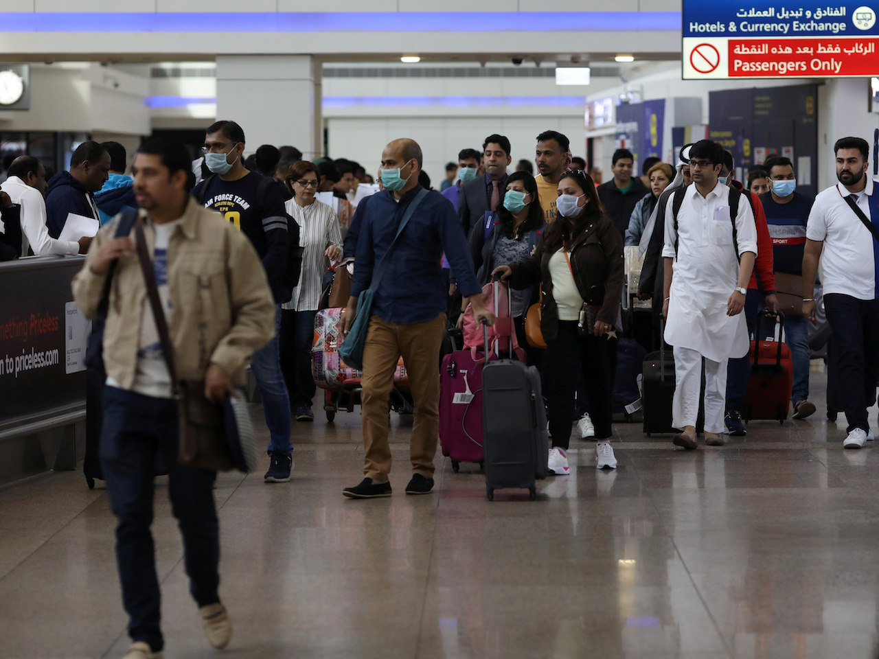 Travellers wear masks as they arrivw at the Dubai International Airport after the UAE's Ministry of Health and Community Prevention confirmed the country's first case of coronavirus in Dubai