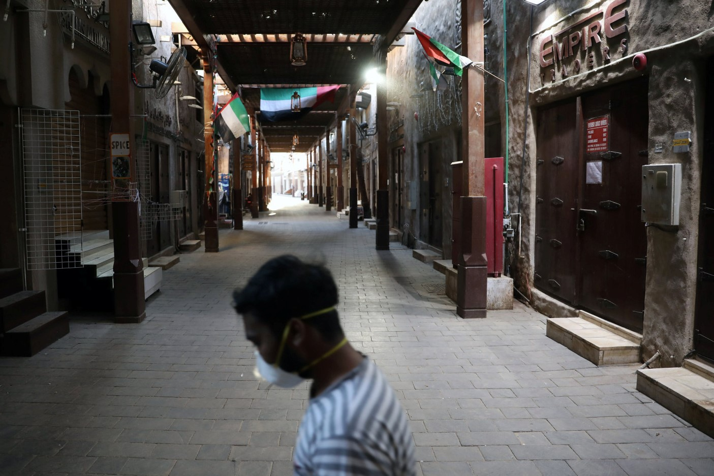 A man wearing a protective face mask walks through the deserted Barajeel Souq, following the outbreak of the coronavirus disease (COVID-19), in old Dubai, United Arab Emirates, March 31