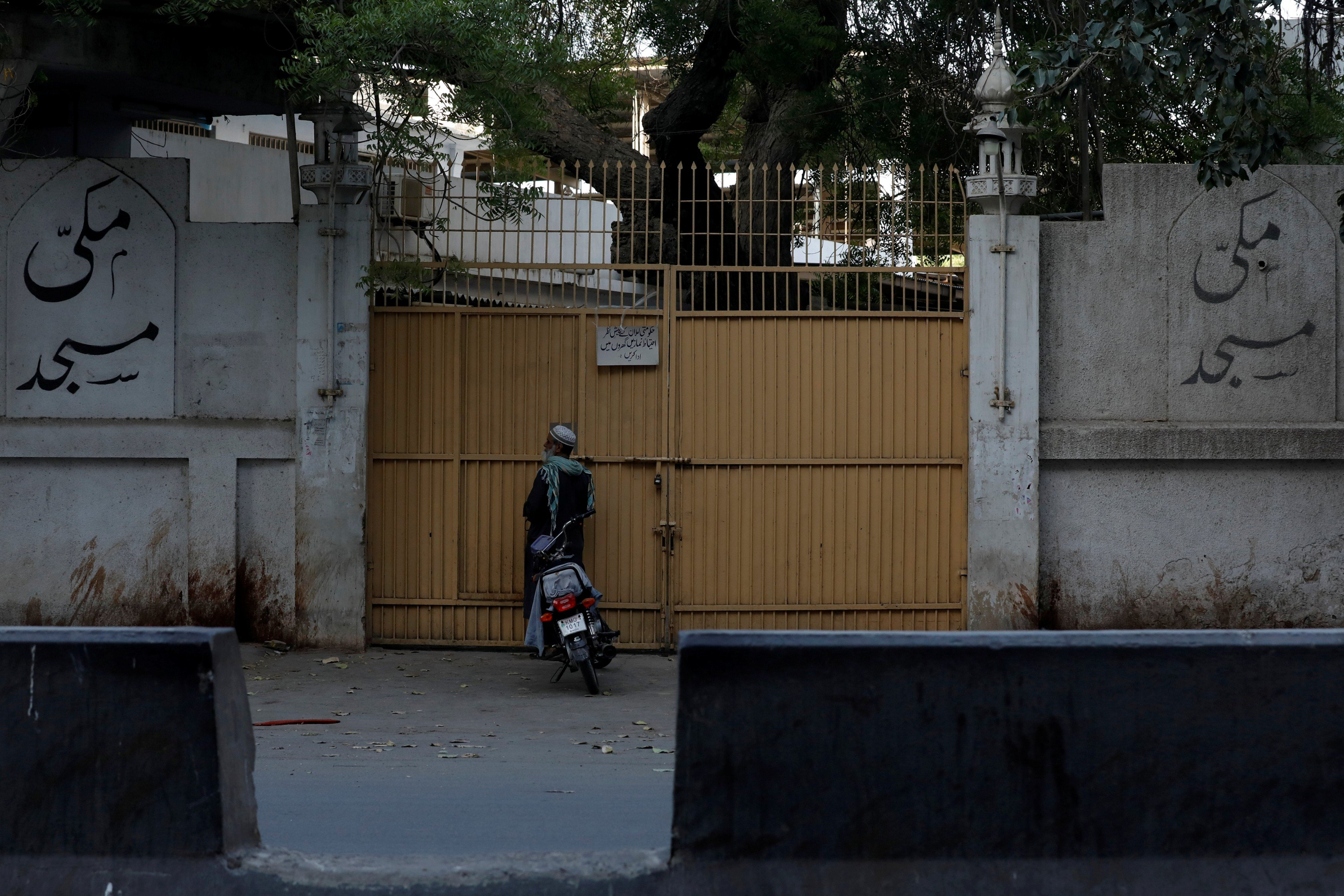 A man stands at the closed entrance of the Makki Masjid Tablighi centre in Karachi this week after the government ordered those inside to quarantine (Reuters)