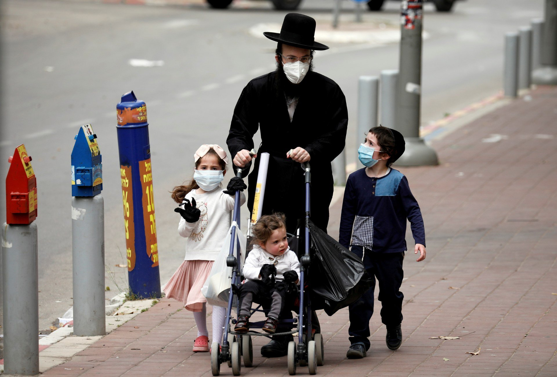 An Ultra-Orthodox Jewish family wearing masks walk on a pavement in Bnei Brak (Reuters)