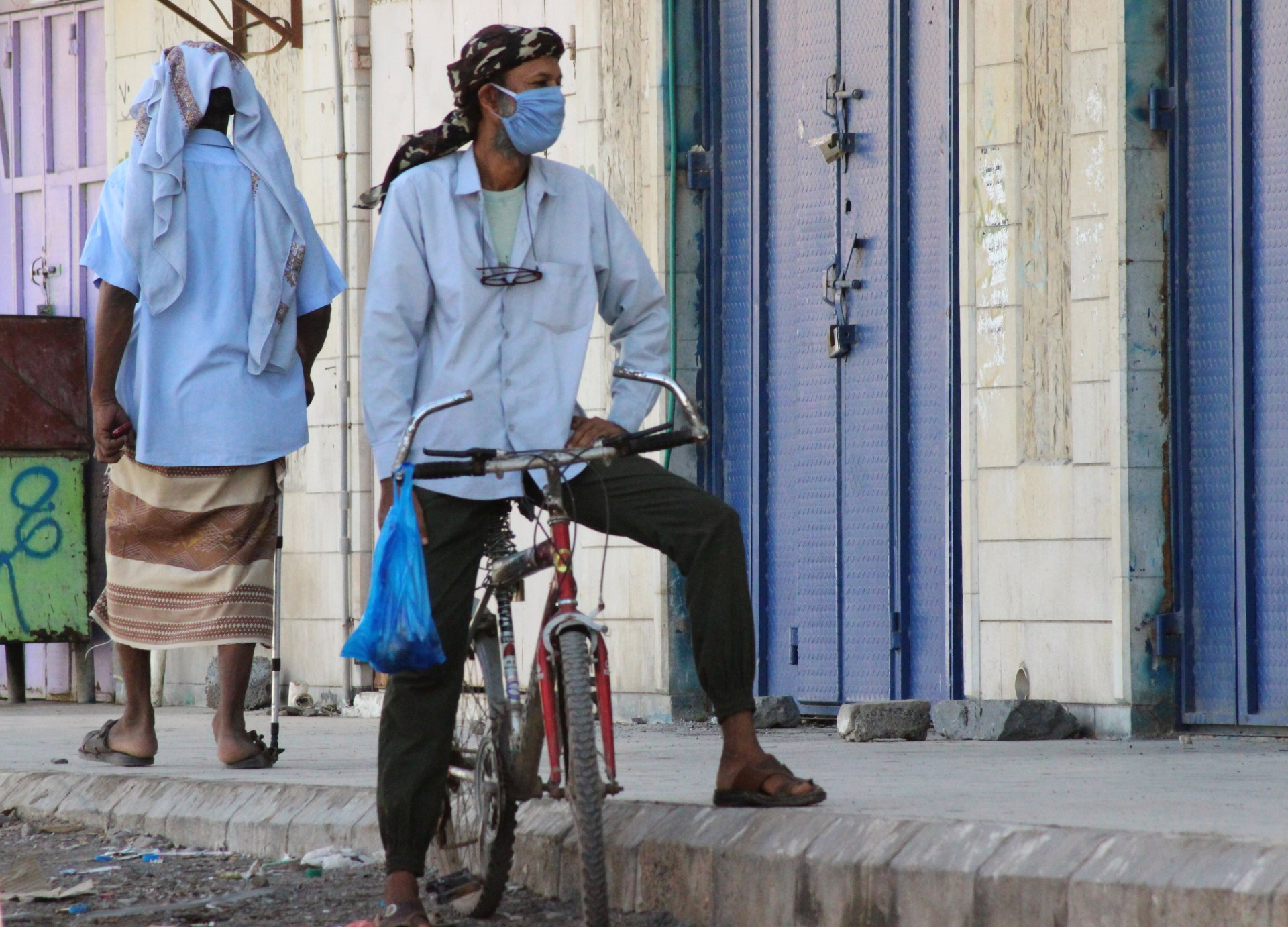 A man wearing a protecitve face mask rides a bicycle during a curfew amid concerns about the spread of the coronavirus disease (COVID-19) in Aden (Reuters)
