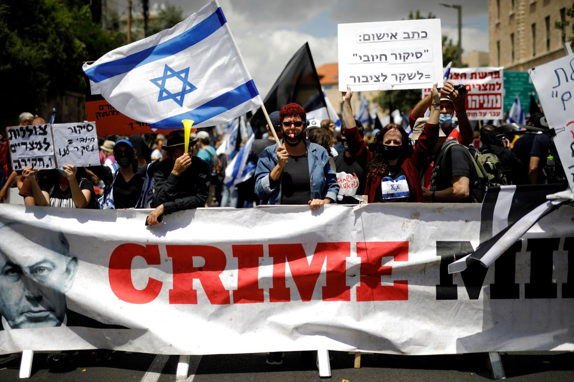 Les manifestants agitent un drapeau israélien et tiennent des pancartes alors qu'ils se tiennent derrière une bannière,